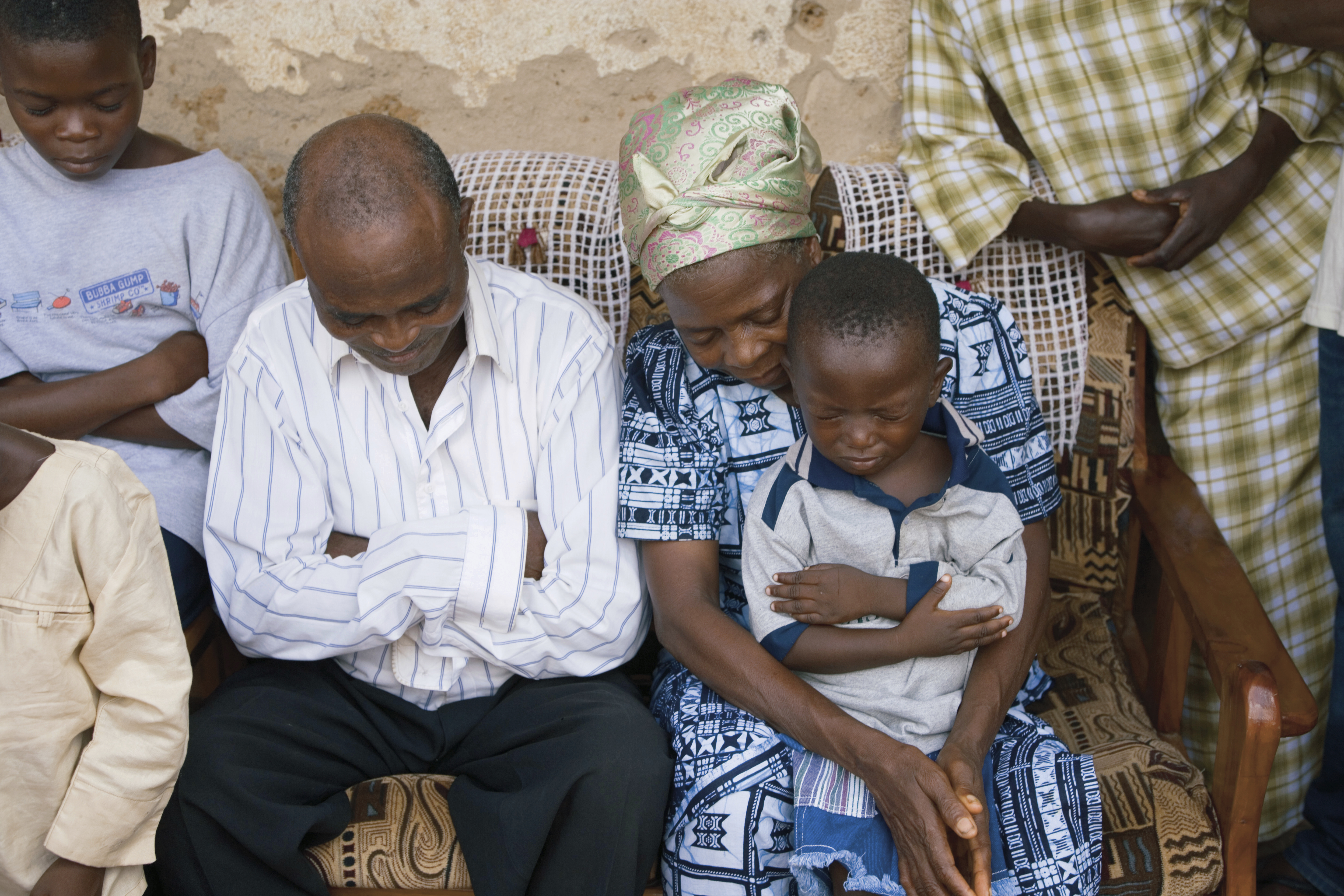 A family in Africa sitting and praying together.