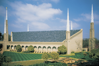 A side view from afar of the Johannesburg South Africa Temple on a sunny day, with a cloudy blue sky in the distance.