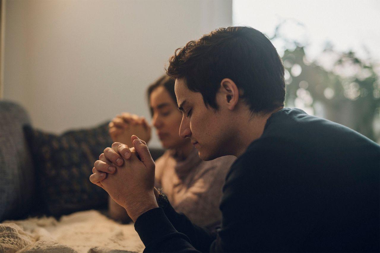 Una pareja se arrodilla para orar juntos a Dios
