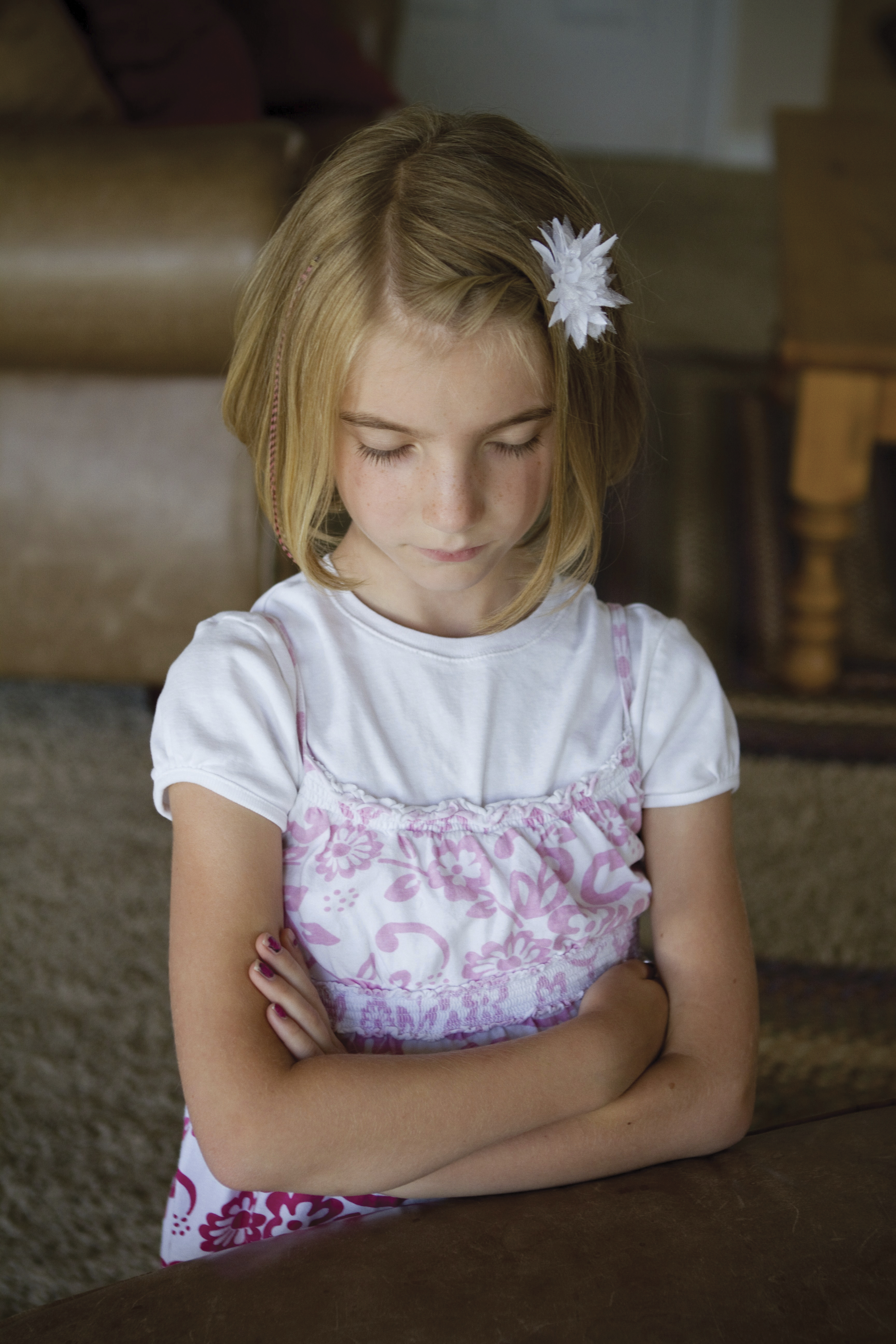 A young girl prays, kneeling in the living room.