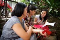 A woman and her two ministering sisters, all in dresses, sit outside on a step in the Philippines as they read from a magazine.