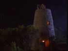 A watchtower at night with candles in small windows