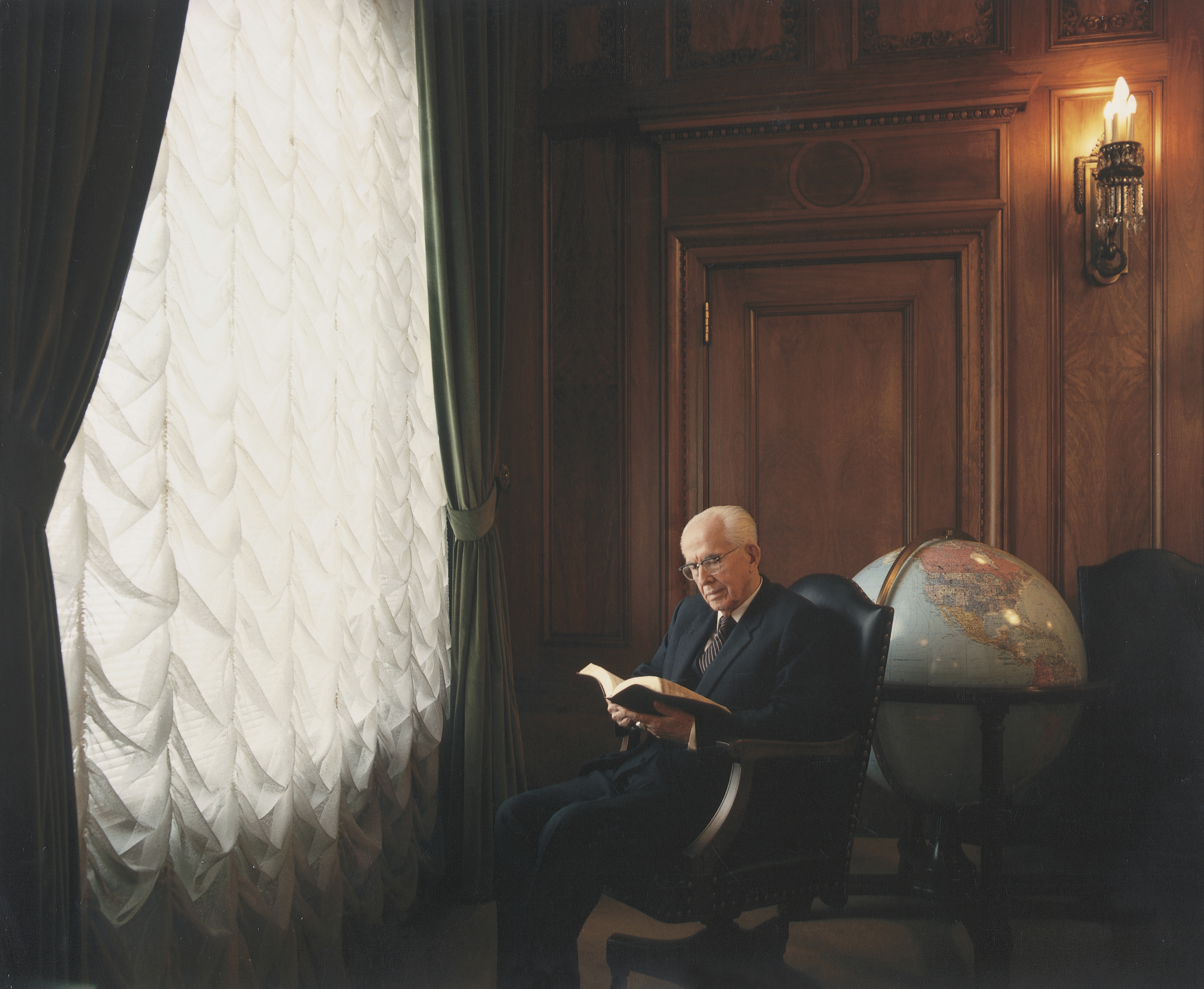President Benson sitting and reading scriptures, with a large globe in the background.
