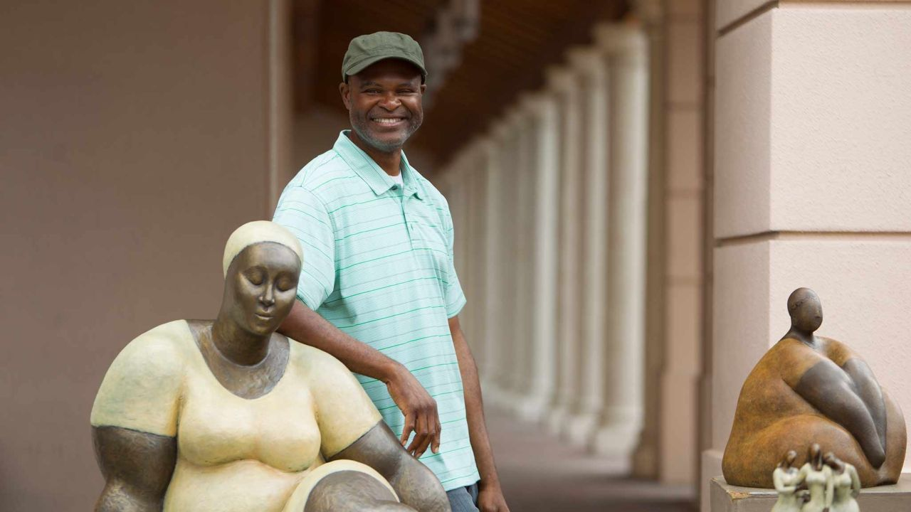A man proudly stands by some of his sculptures