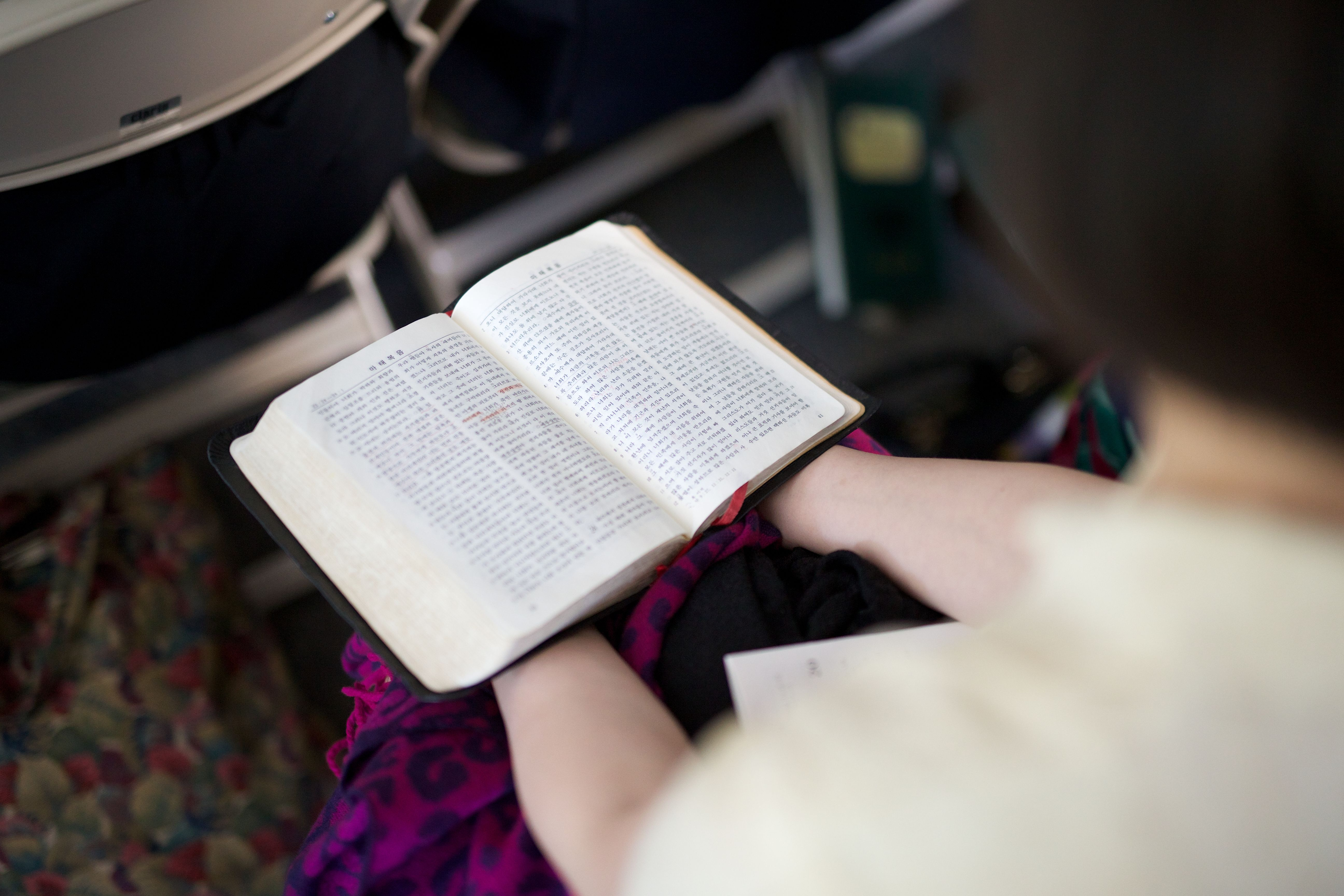 A young woman holds the scriptures during class.