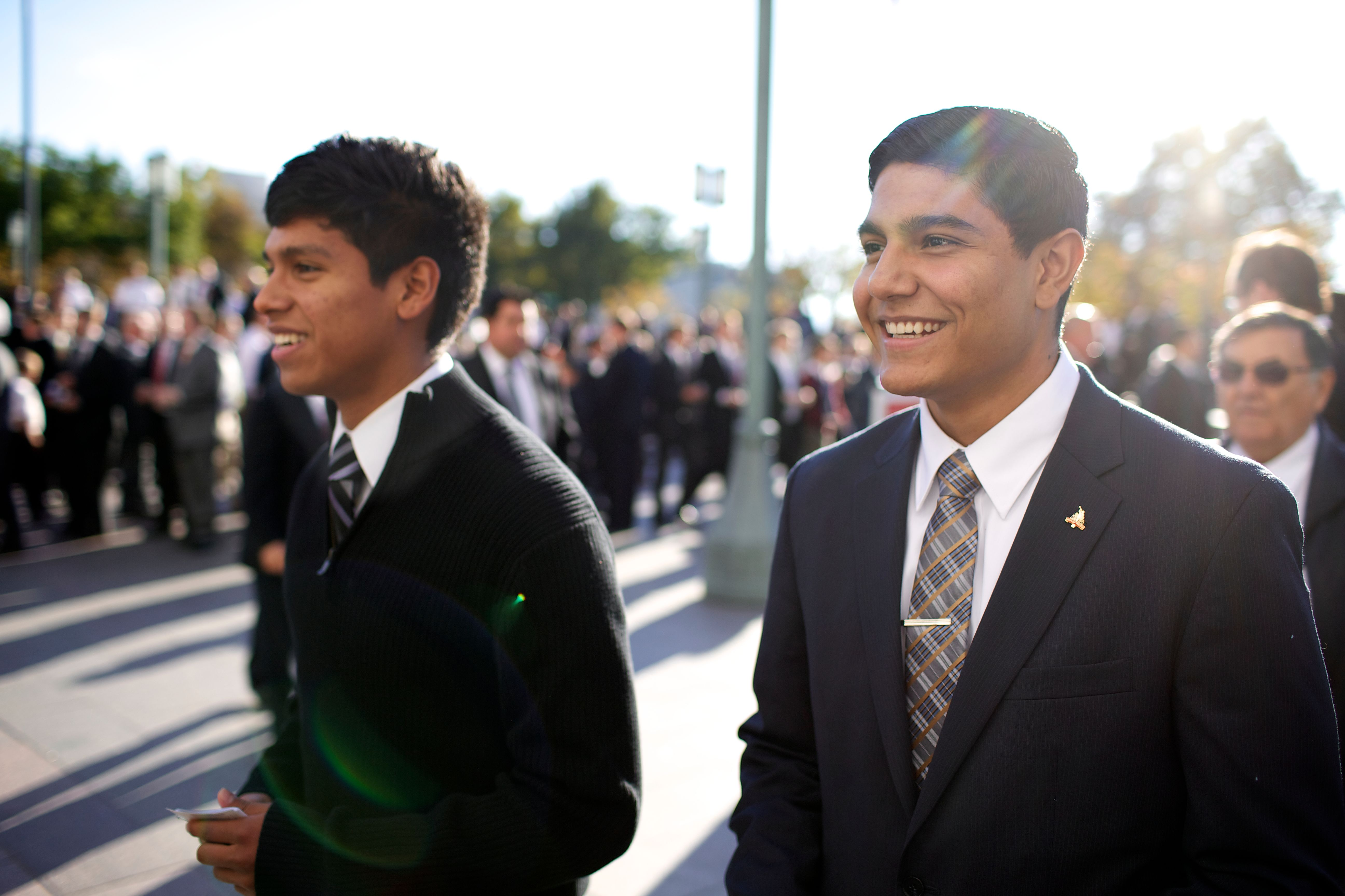 Two young men standing outside with other men while waiting for the priesthood session.