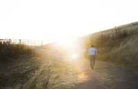 Man walking up a path at sunset