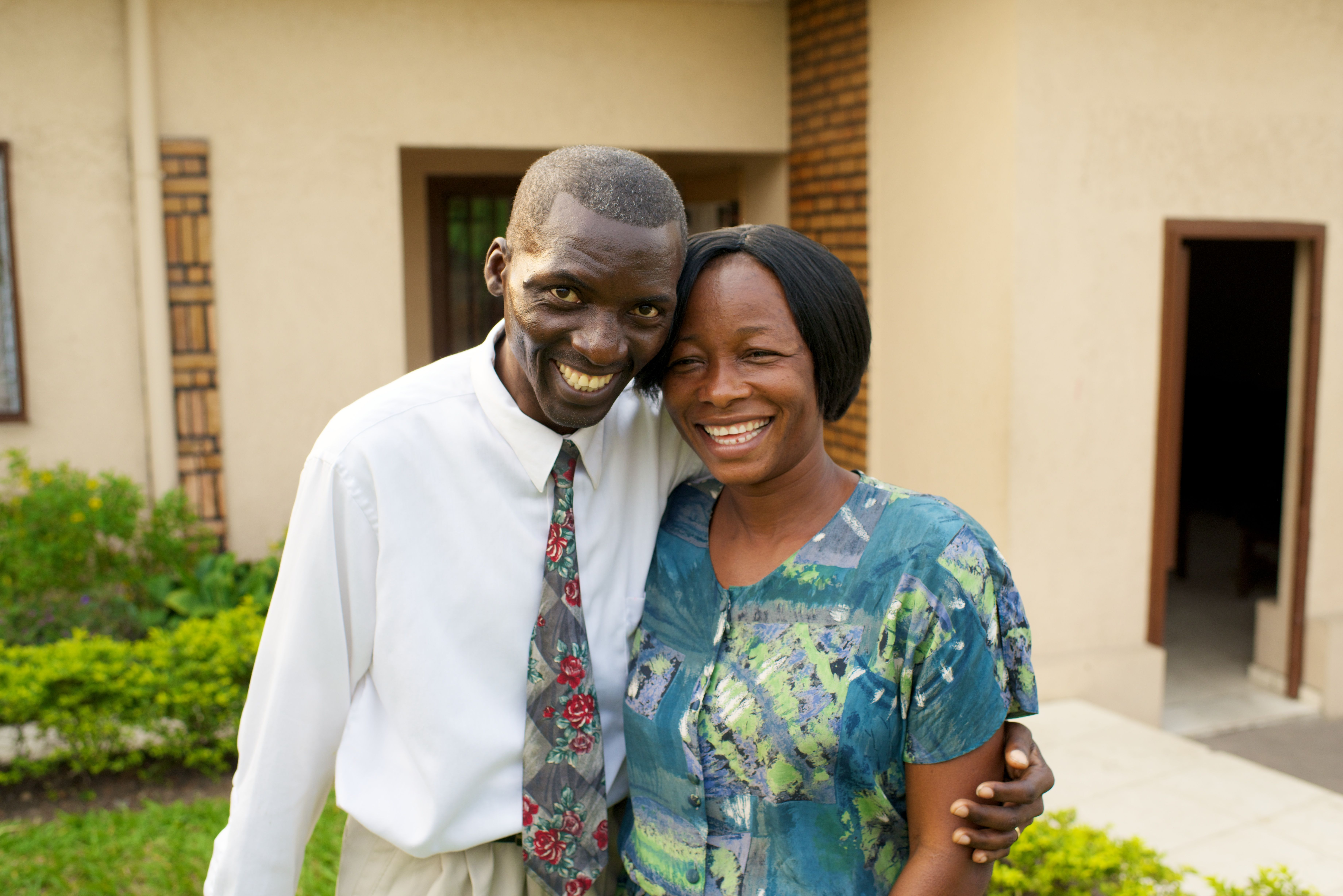 A husband and wife standing beside each other outside in Africa.