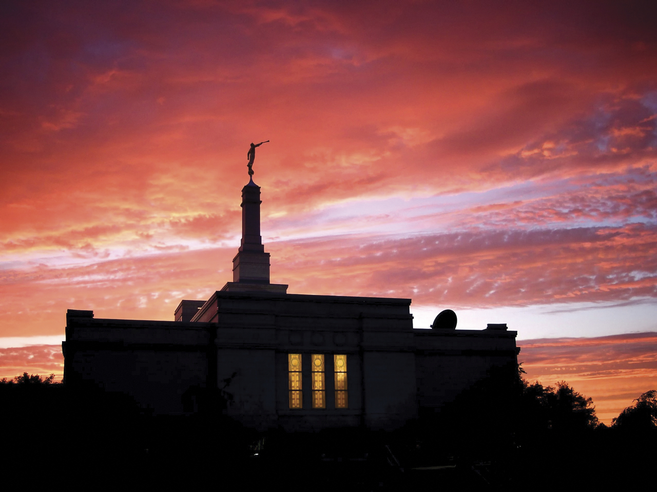 A silhouetted photograph of the Halifax Nova Scotia Temple at sunset, with a red sky behind it and a window glowing yellow from within.
