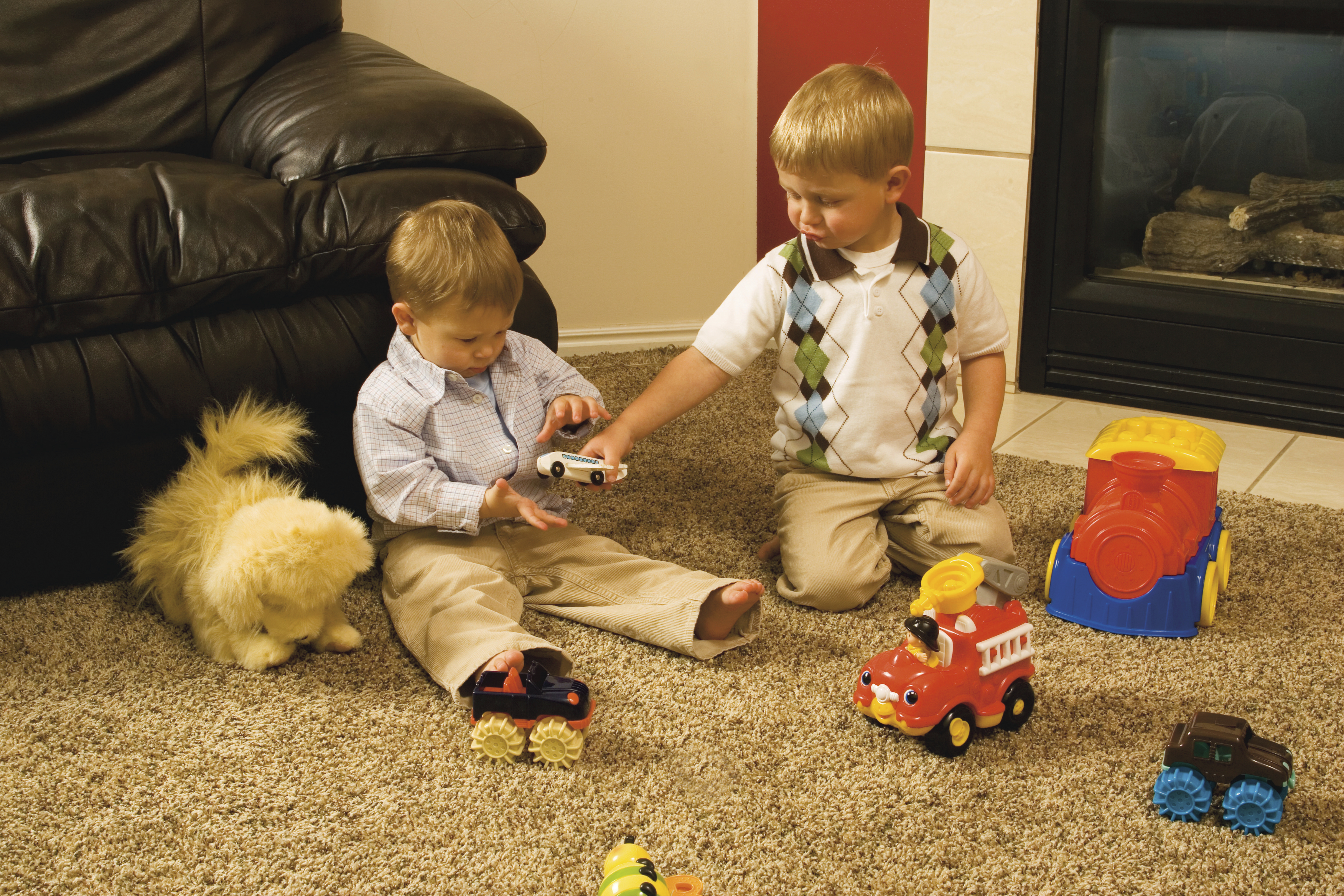 Two young brothers play with cars on the floor together.