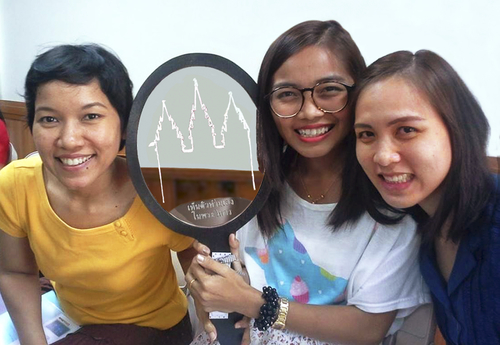 """Thai young women with a mirror that says, """"See Yourself in the Temple."""""""