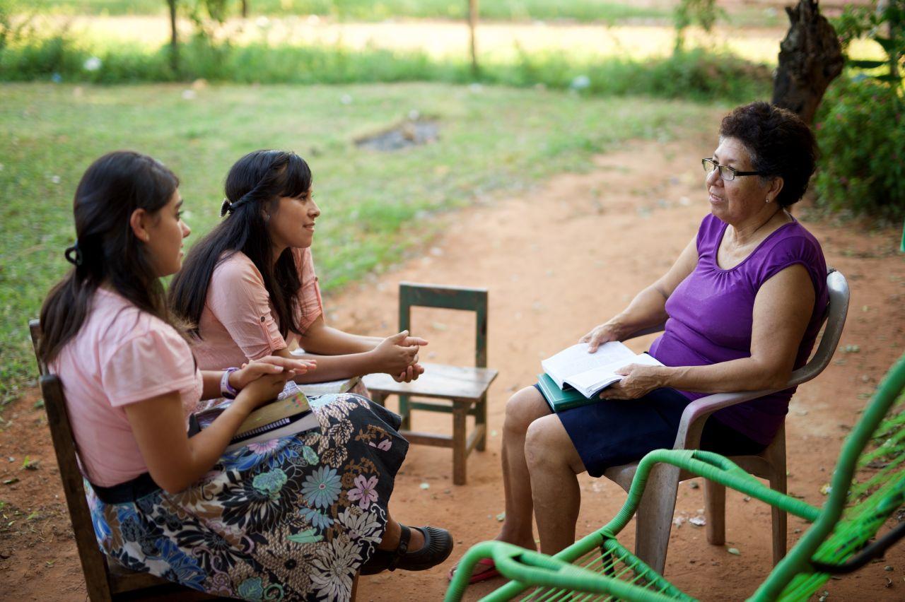 par de hermanas misioneras enseñando a una mujer
