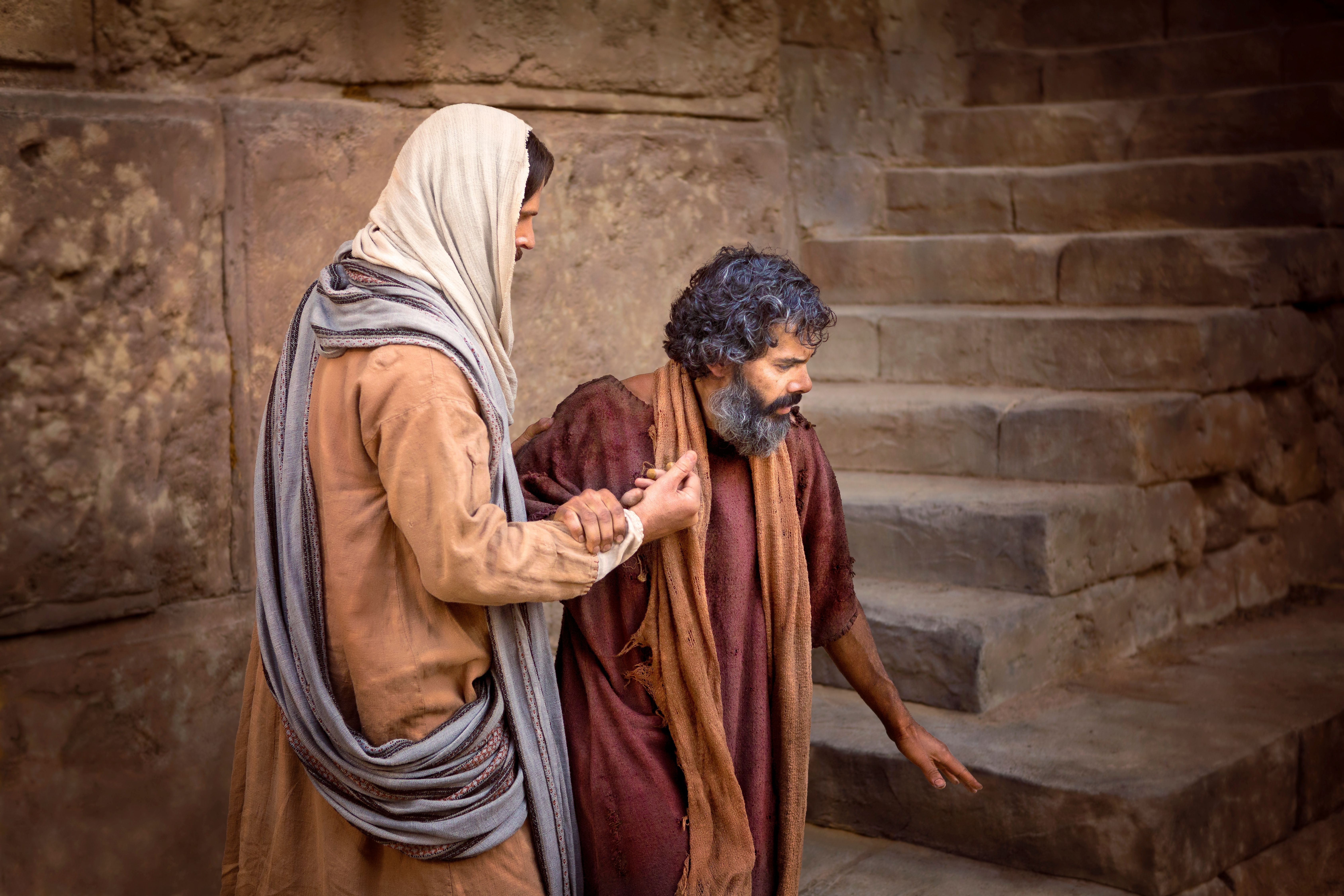 Jesus standing and healing a blind man.
