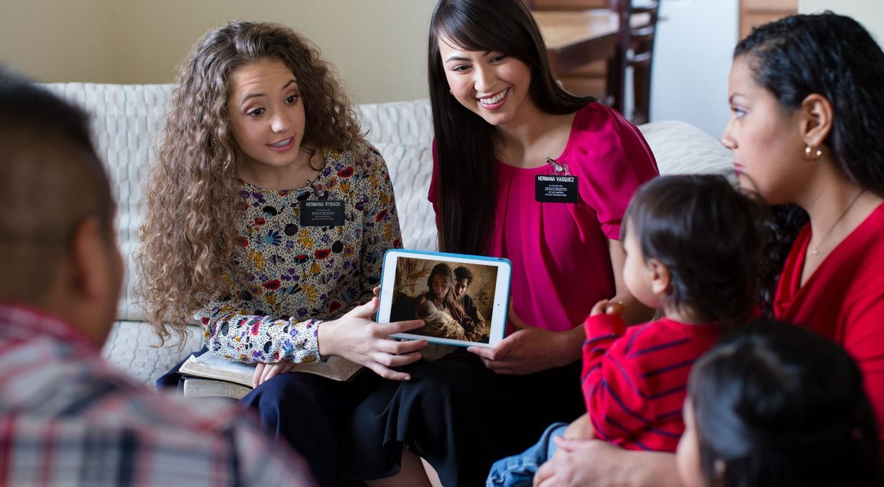 Two sister missionaries teach a family about the birth and gospel of Jesus Christ