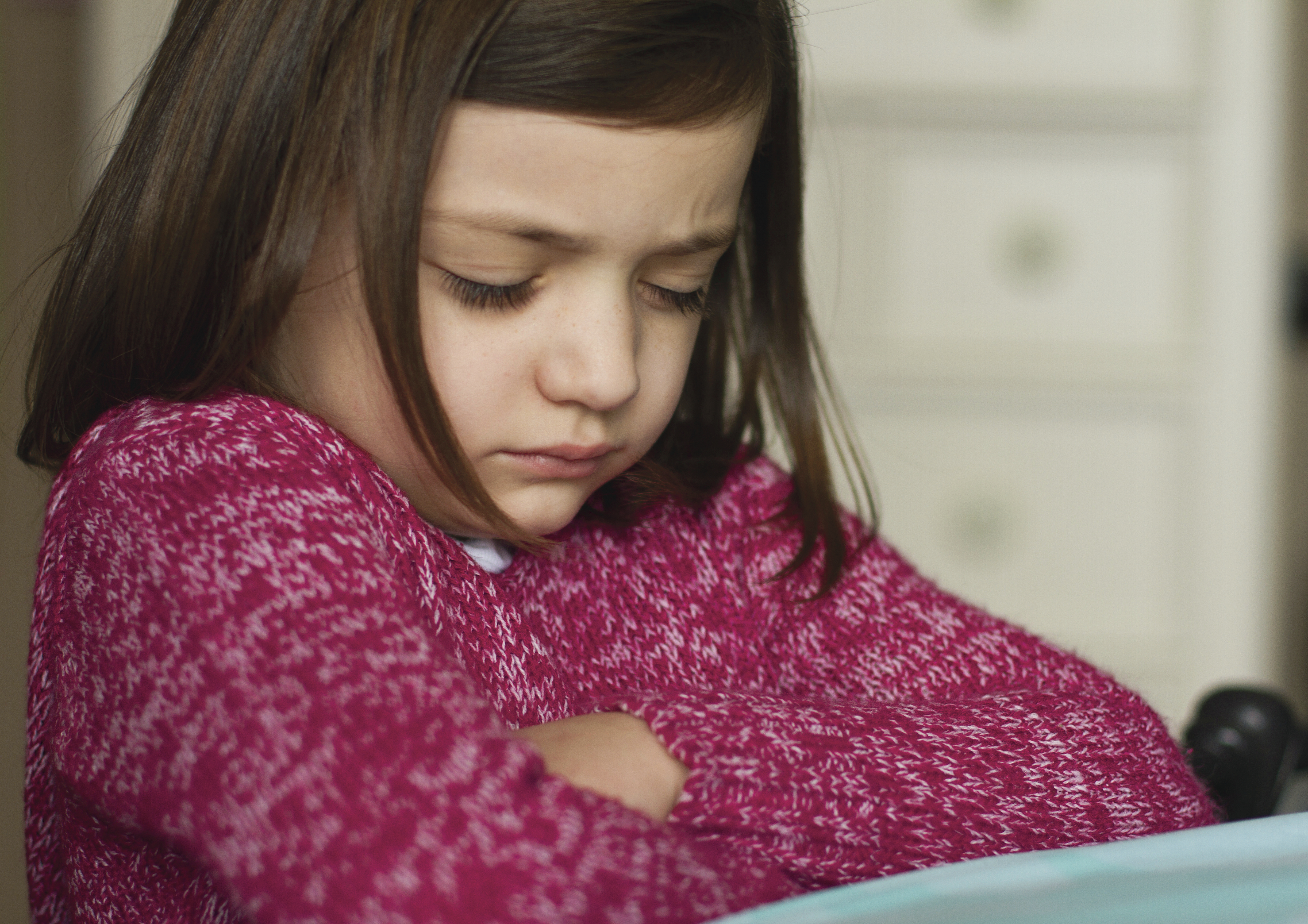 A young girl in a pink sweater folds her arms and prays.