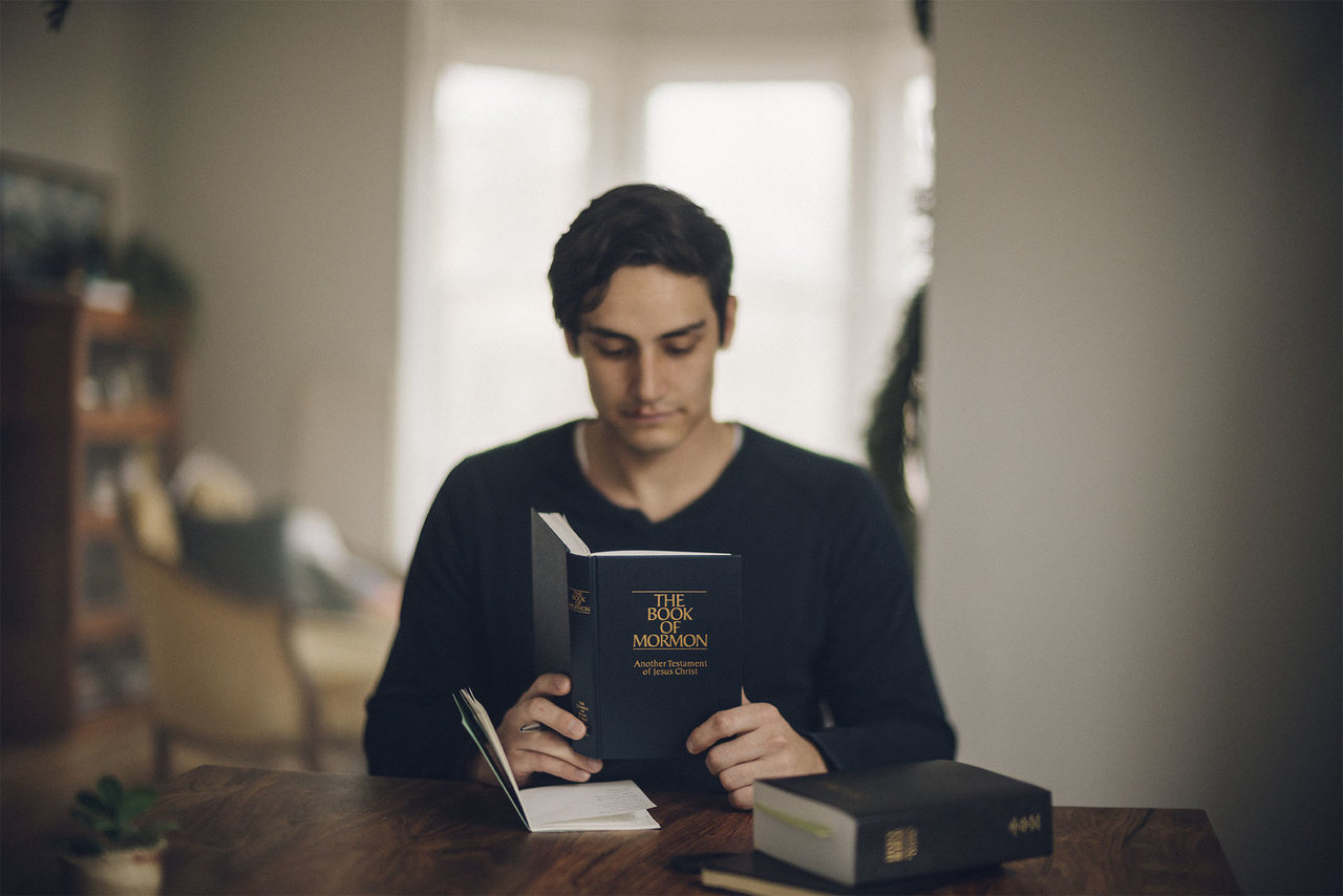A man studies the Book of Mormon and the Bible at his kitchen table