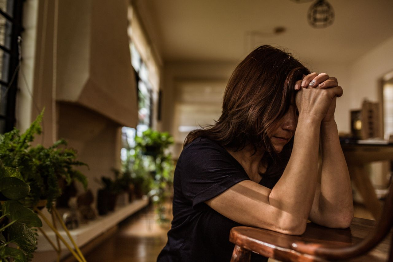 A woman prays at her kitchen table