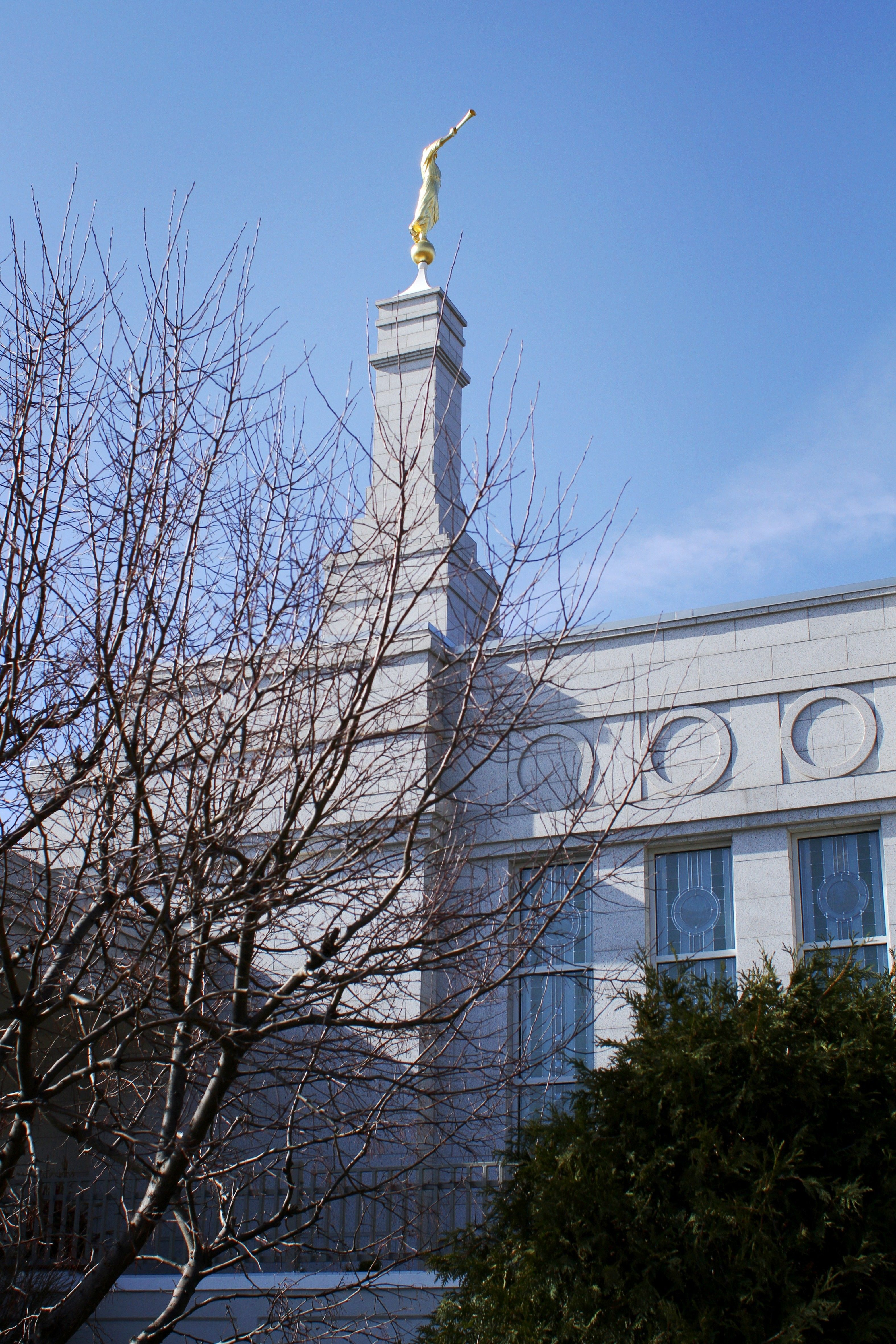 A side view of the St. Paul Minnesota Temple, including the spire, windows, and scenery.