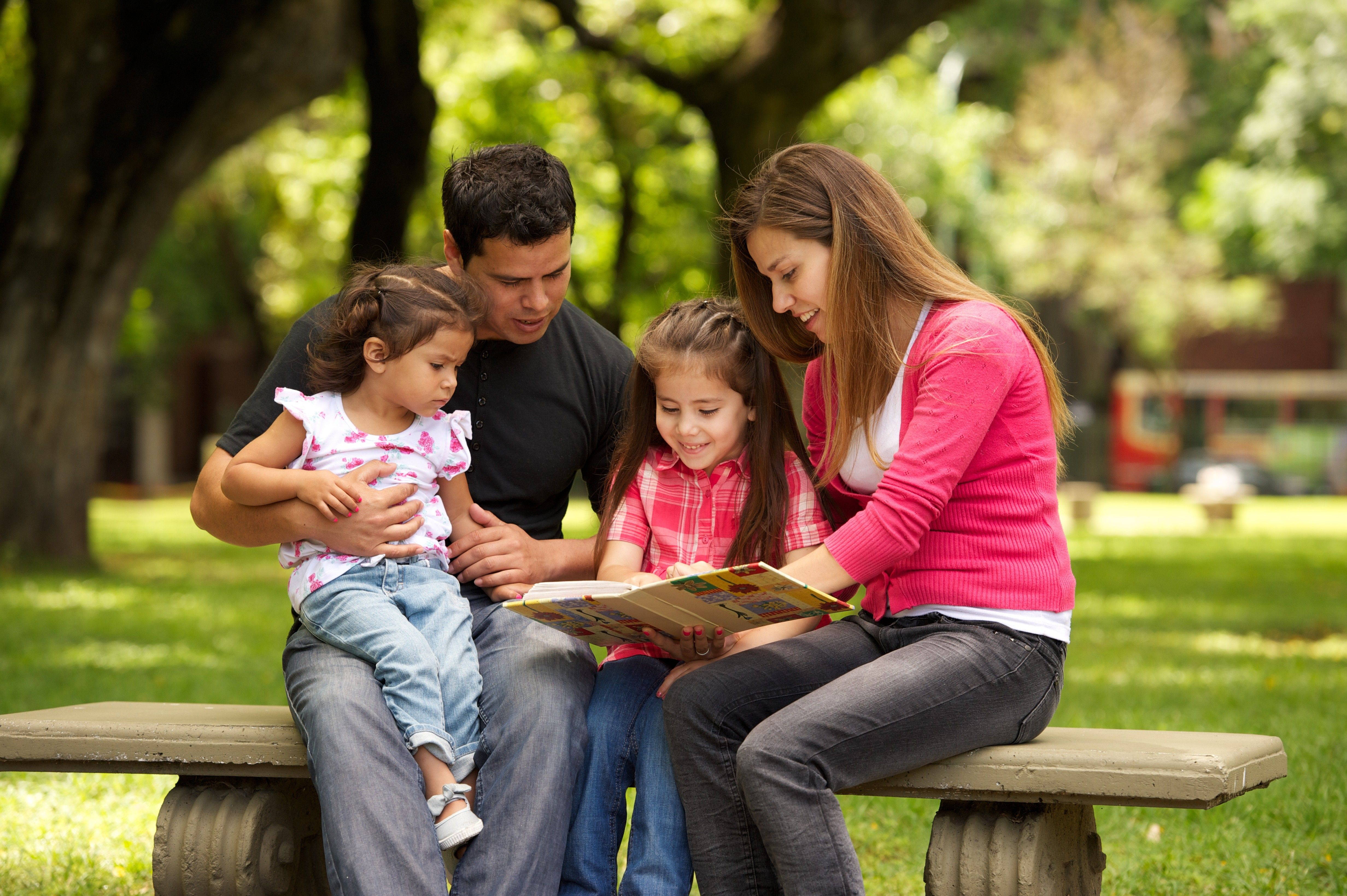 A family reading together in the park.