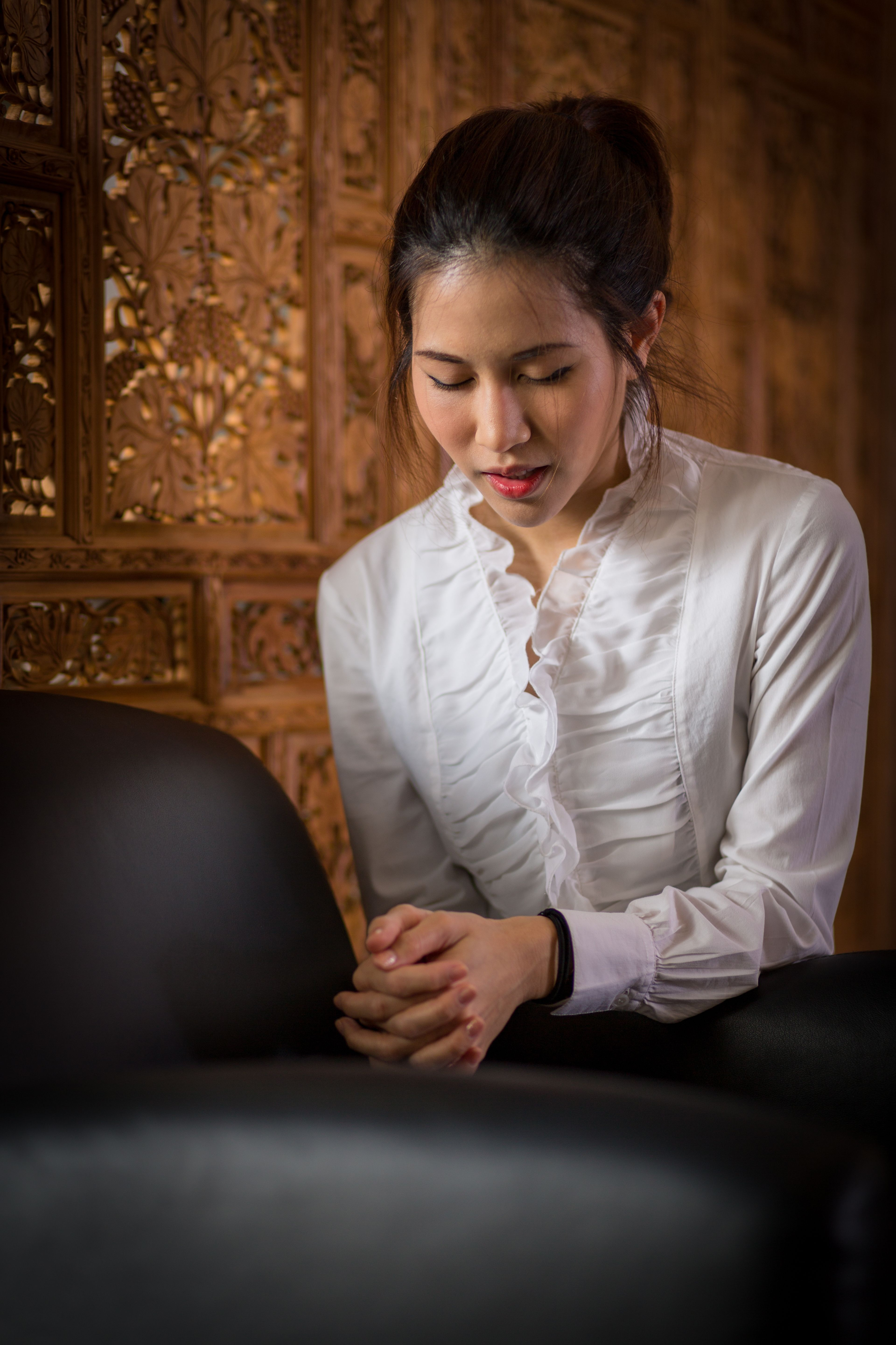 A young woman in Thailand kneels by a chair and prays.
