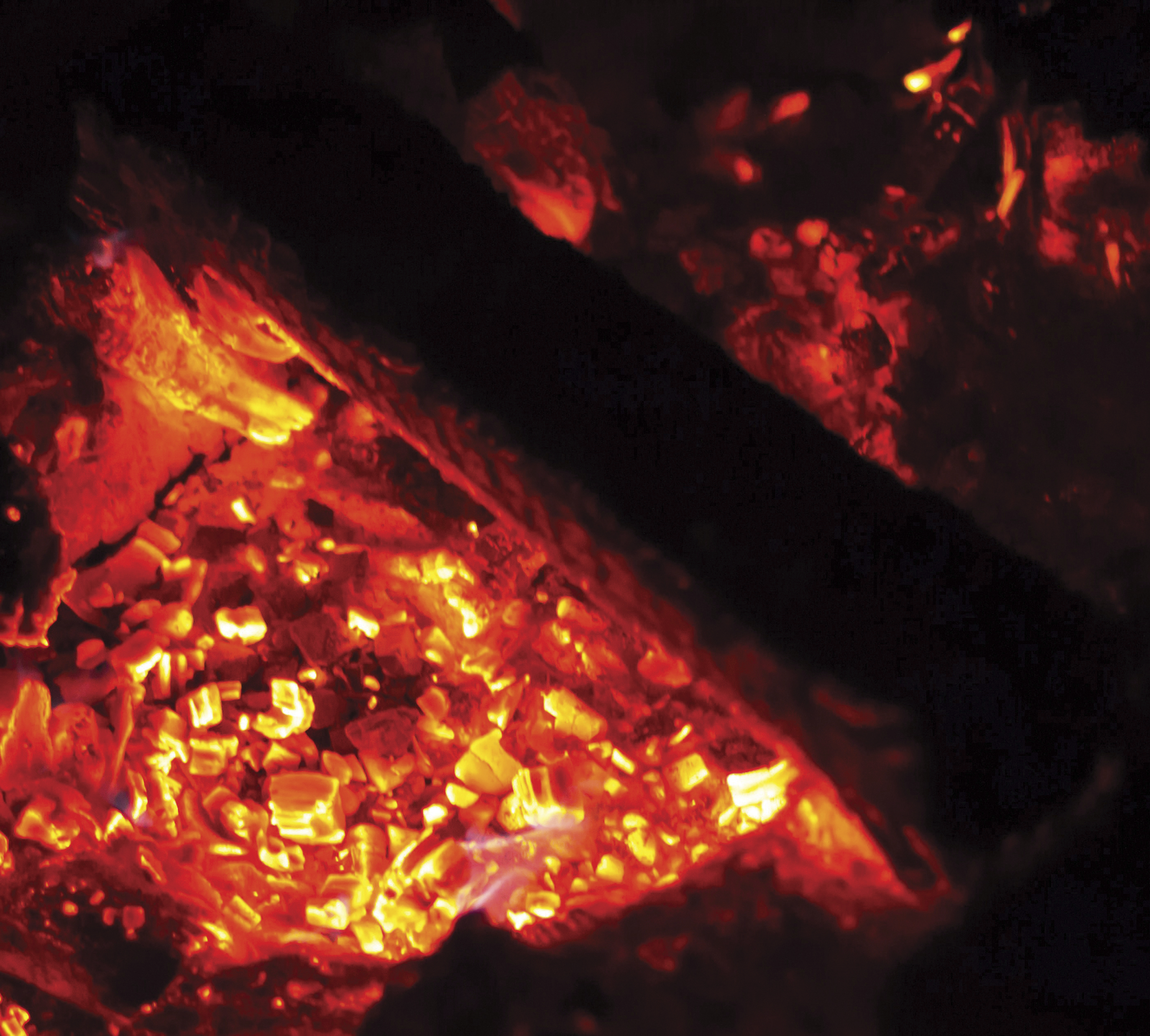 Glowing red embers in a fire pit.