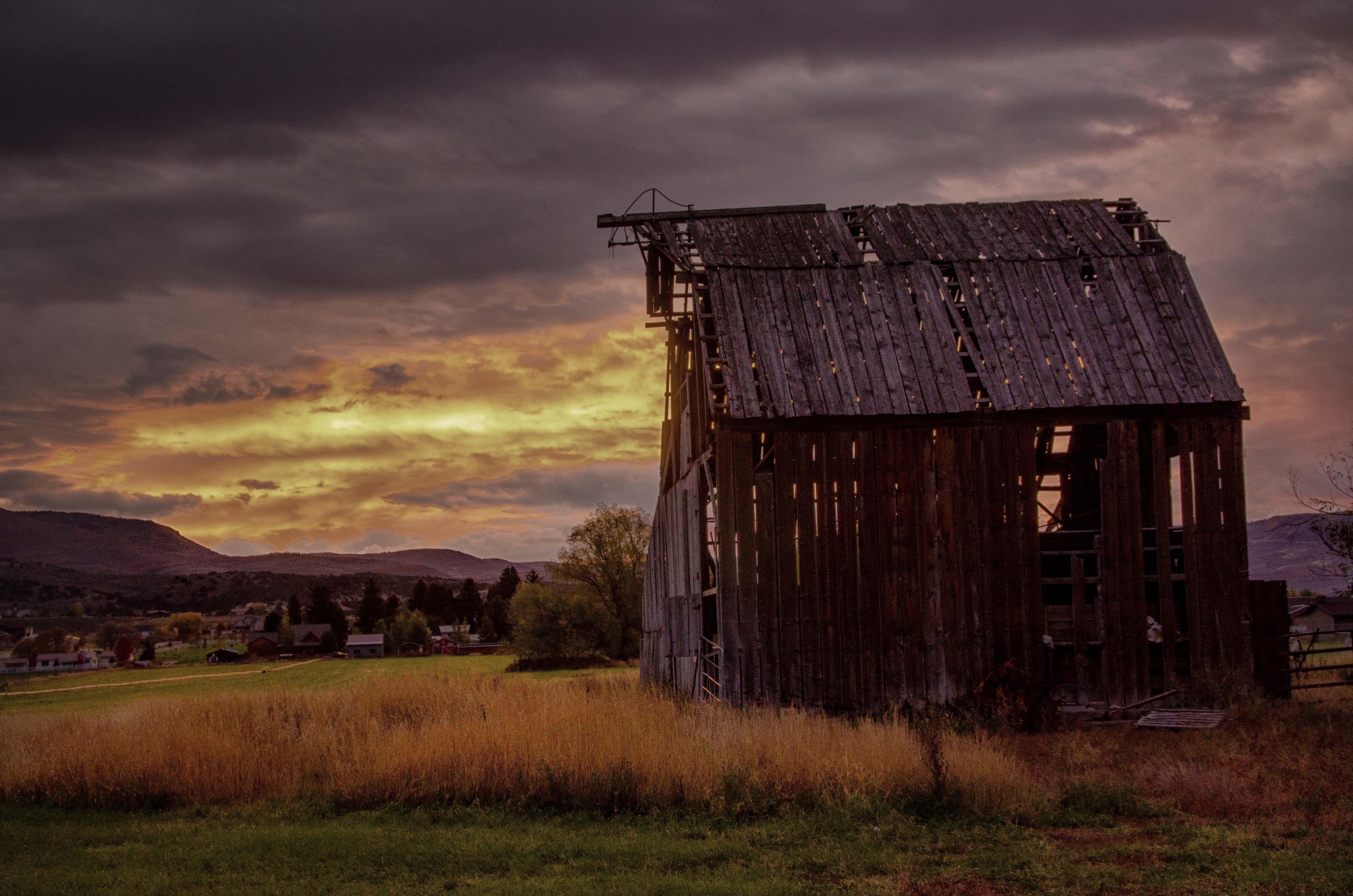 Sunrise over a run-down barn in Utah.