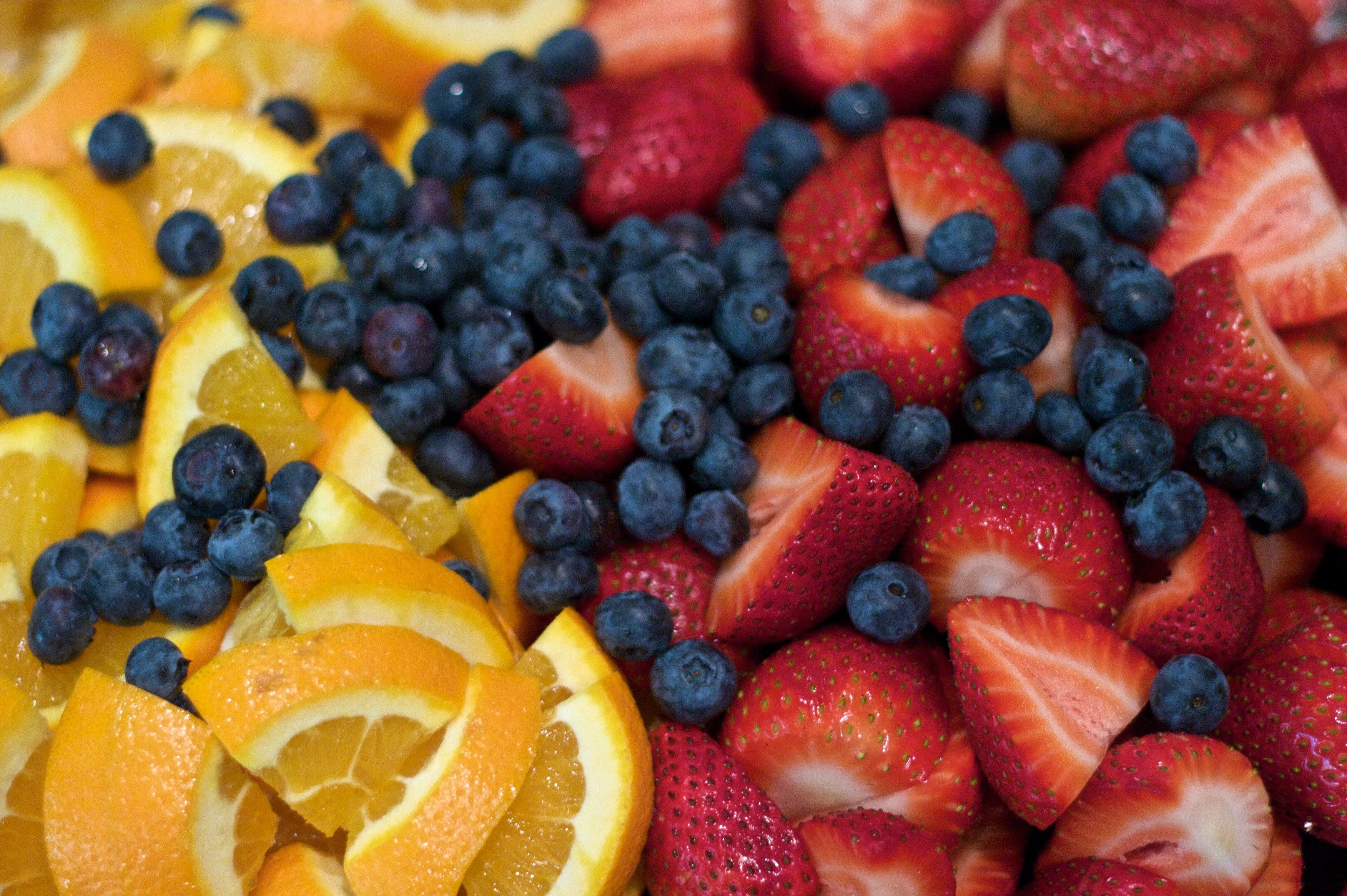 A combination of orange slices, blueberries, and strawberries.