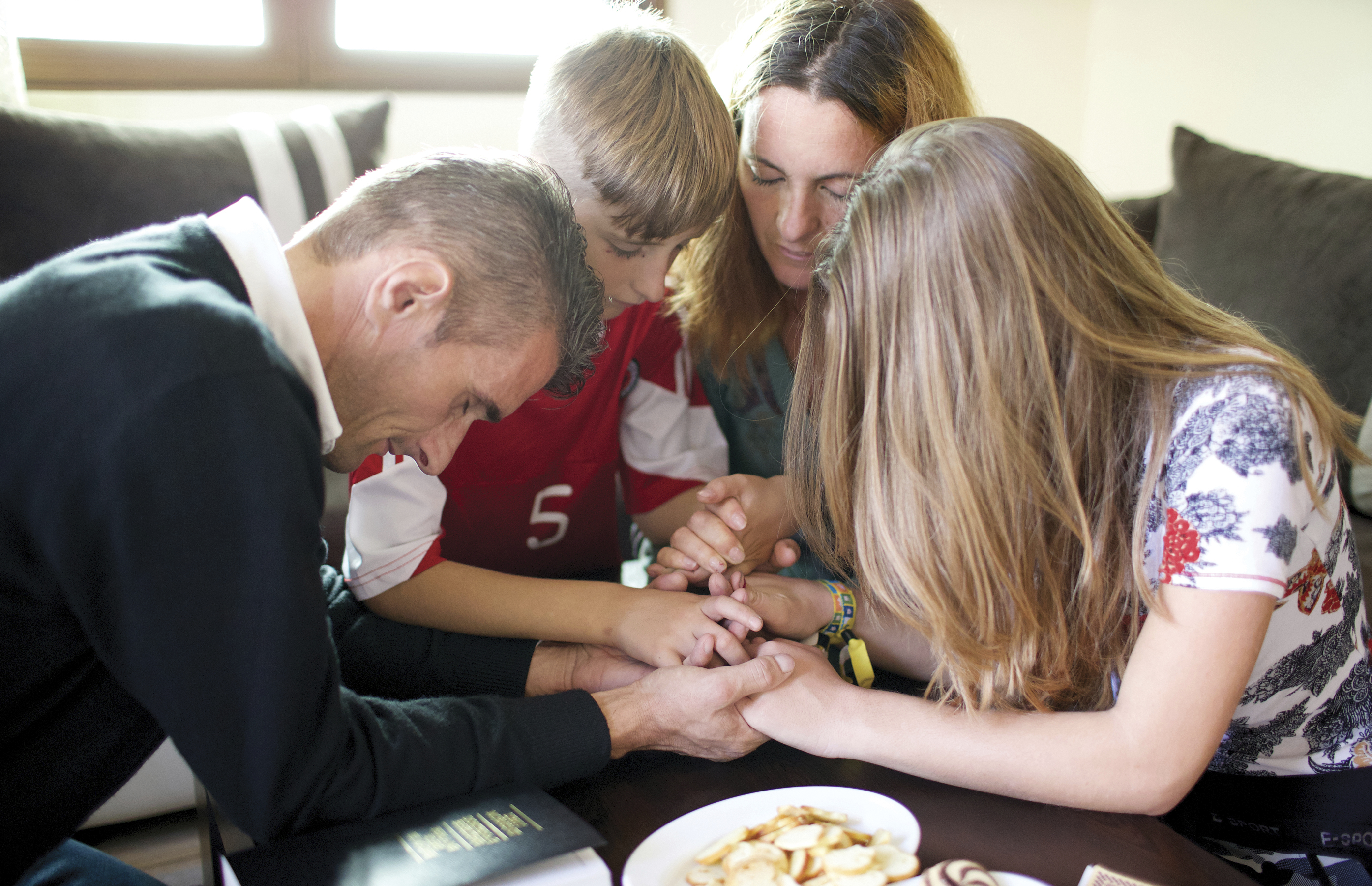 Ilir and his wife Gjystina kneel in prayer with their children.