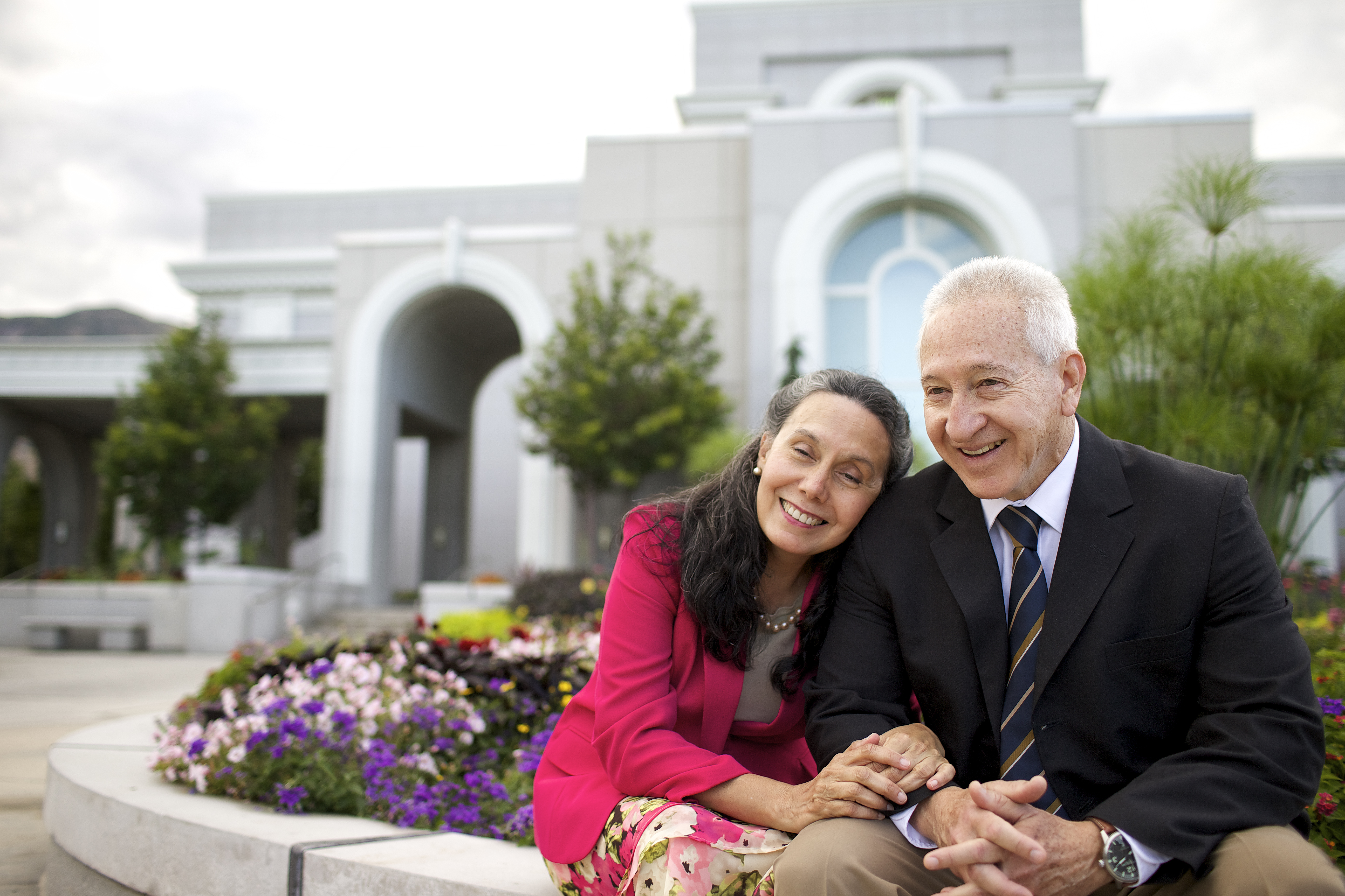 An elderly couple sitting in front of the Mount Timpanogos Utah Temple.