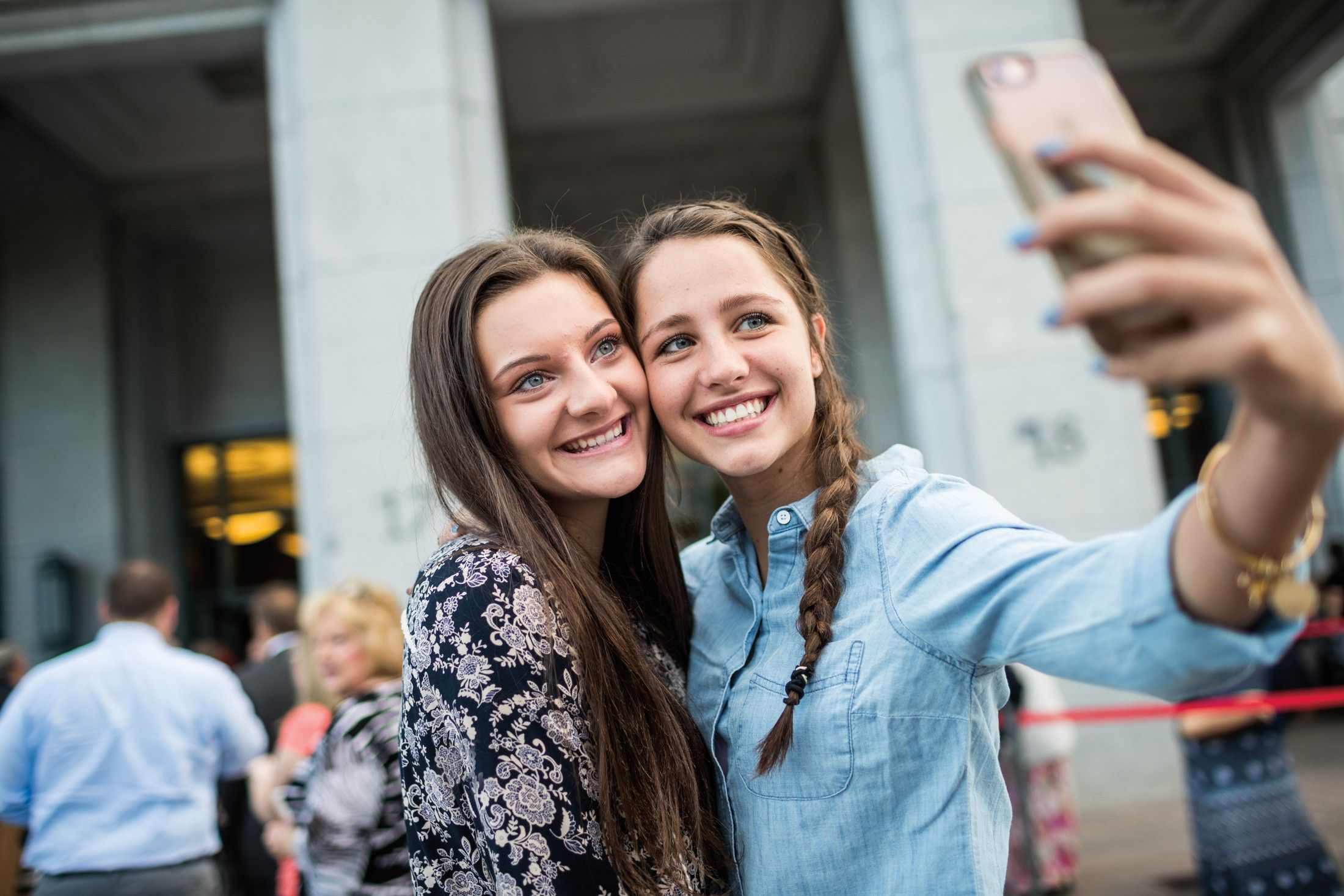 Two teenage girls take a selfie outside of the Conference Center while attending general conference.