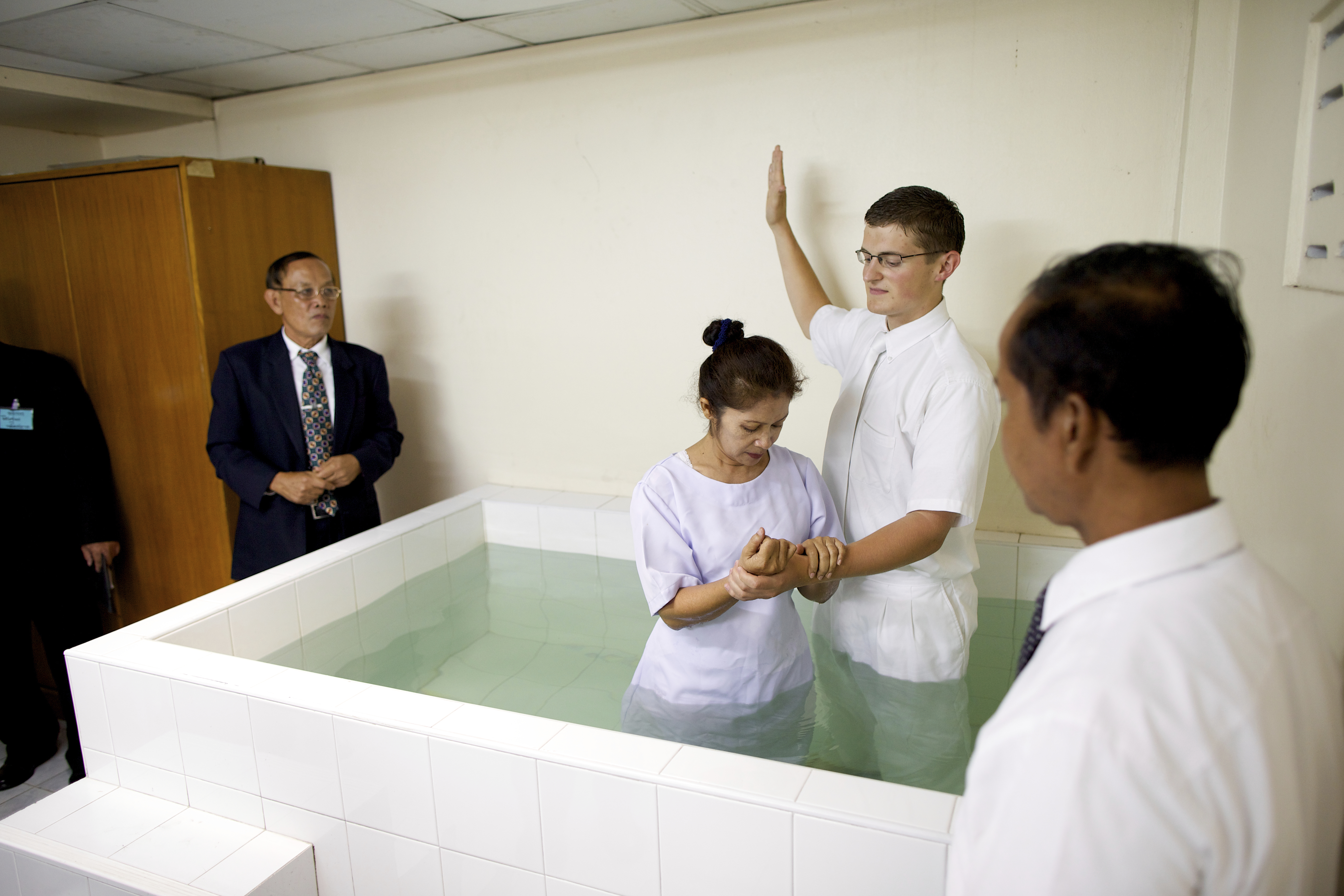 The baptism of a woman in a font in Thailand.