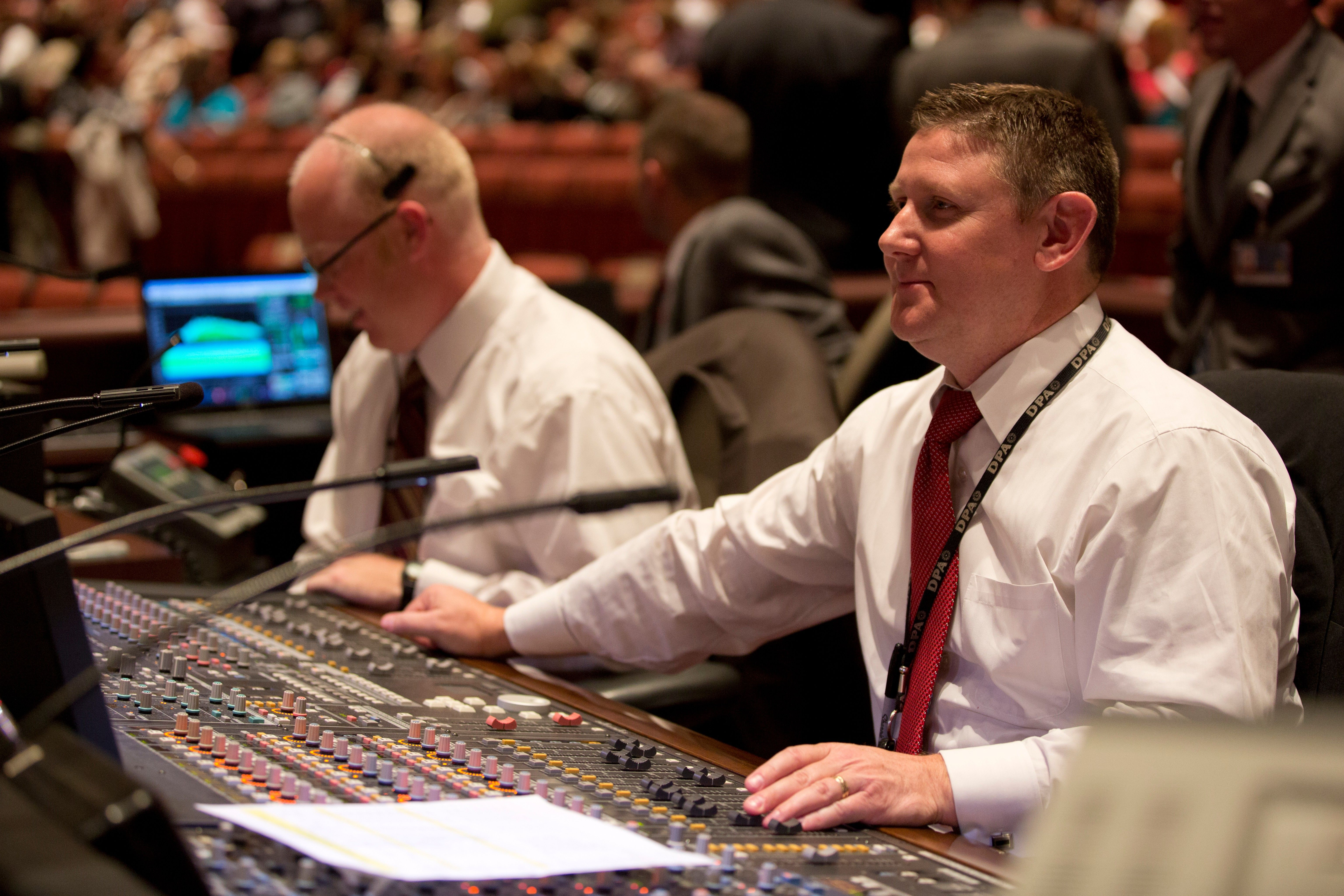 Two men working for the technical crew at general conference.