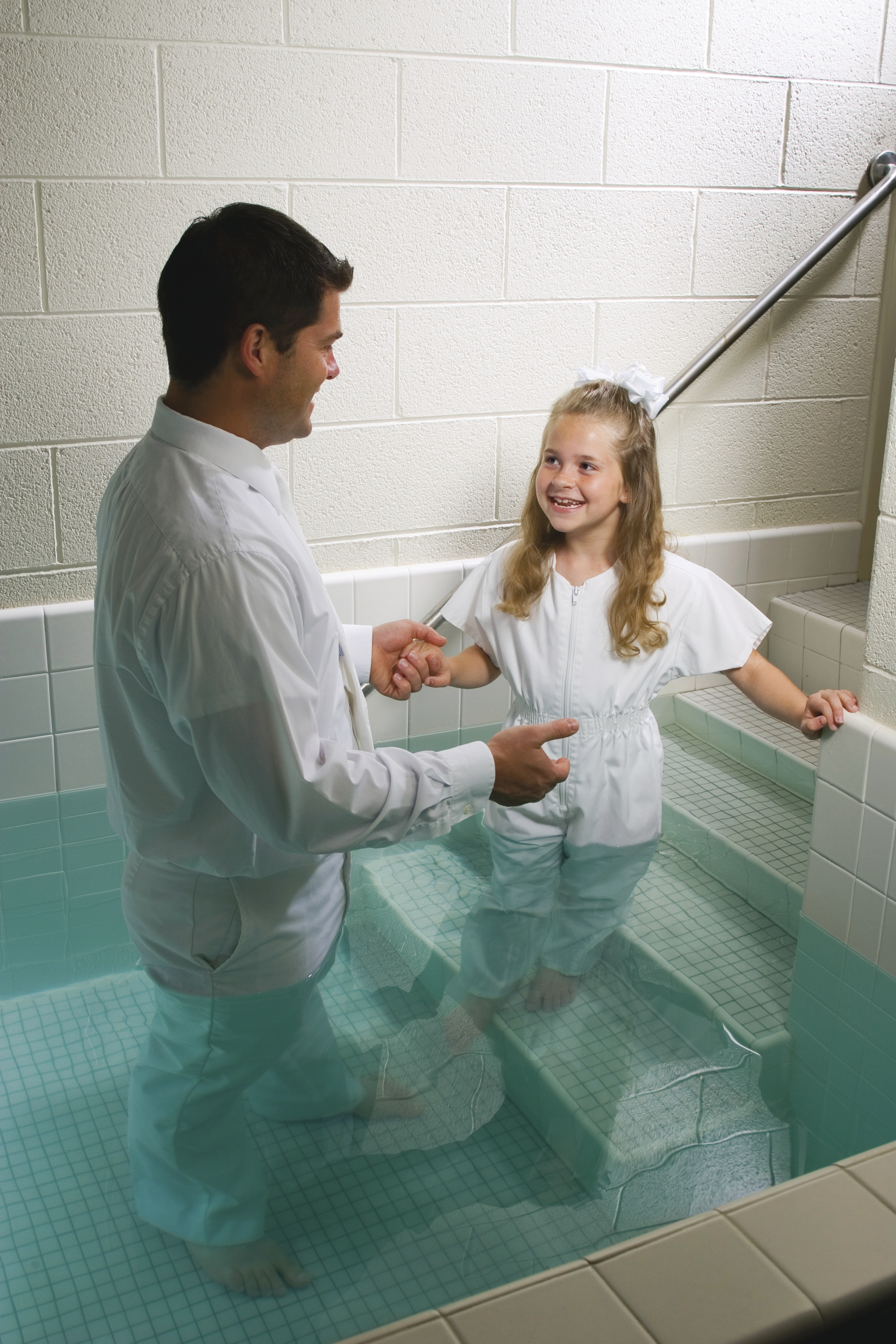 A father leads his young daughter into the baptismal font.