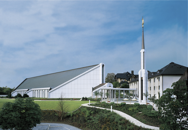 A view of the Frankfurt Germany Temple and its spire on a sunny day, with a blue sky above and green lawns in the front.