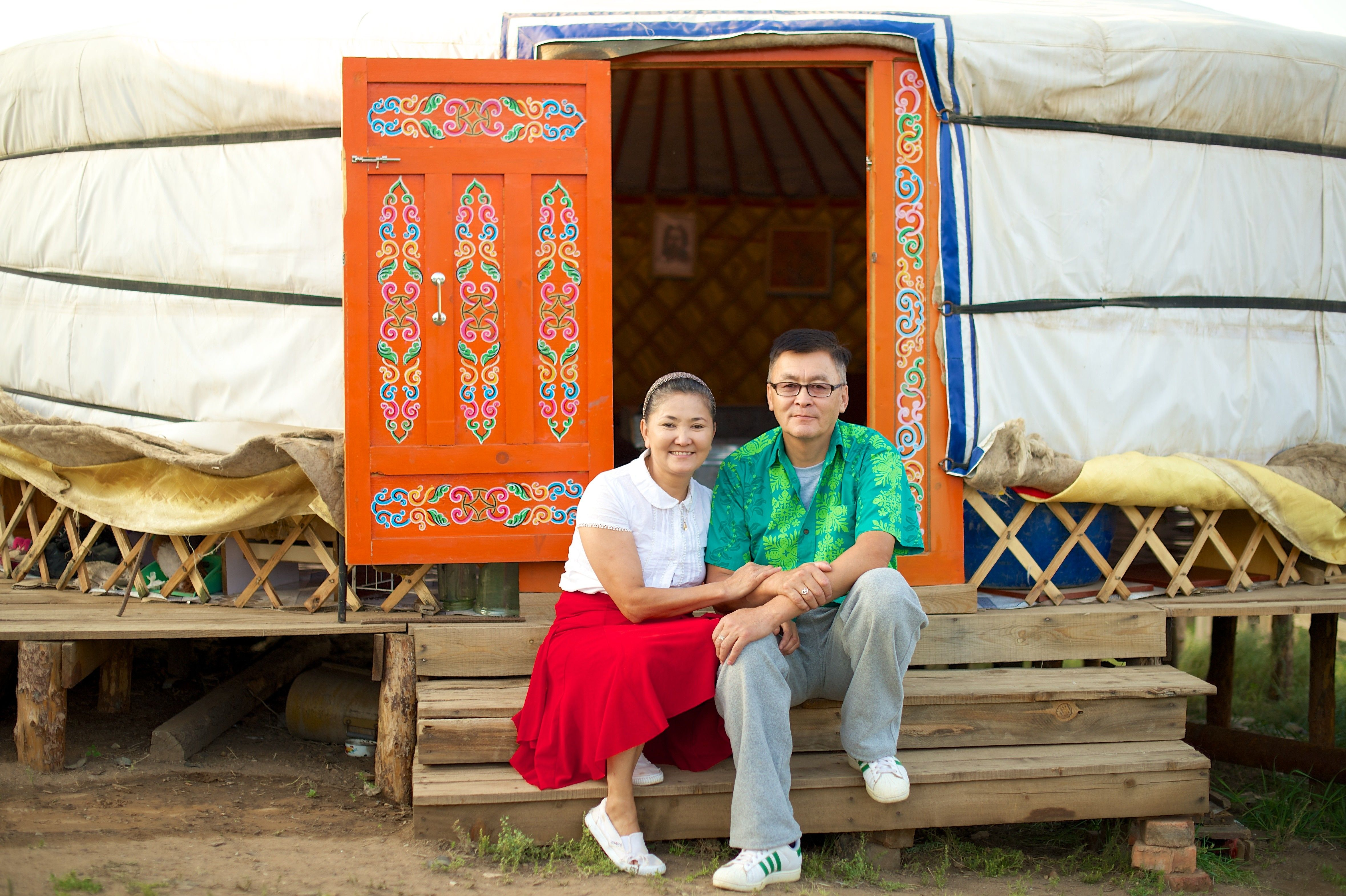 A couple from Mongolia sits on stairs by an orange door that is open.