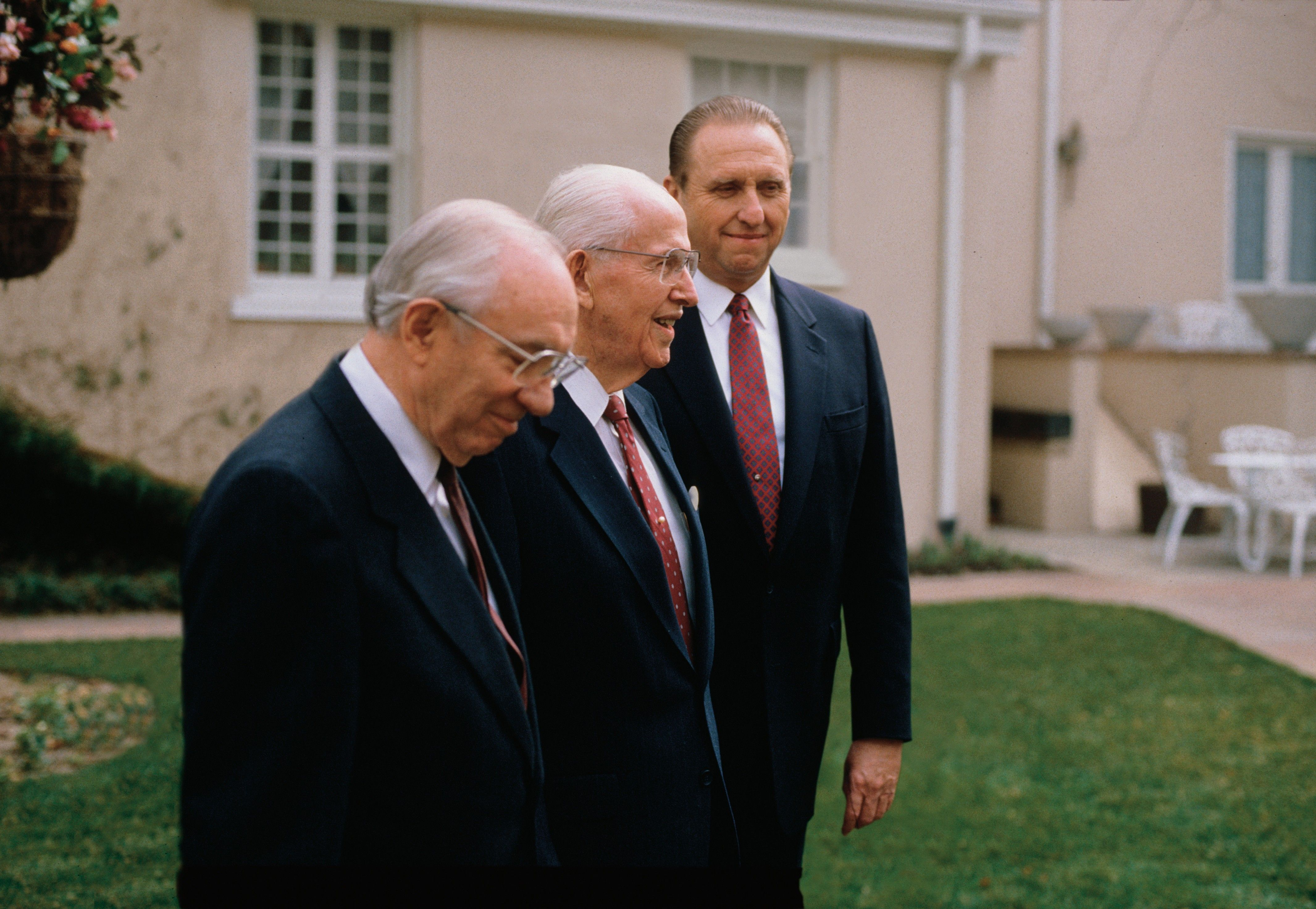 President Benson standing outside with his counselors in the First Presidency.