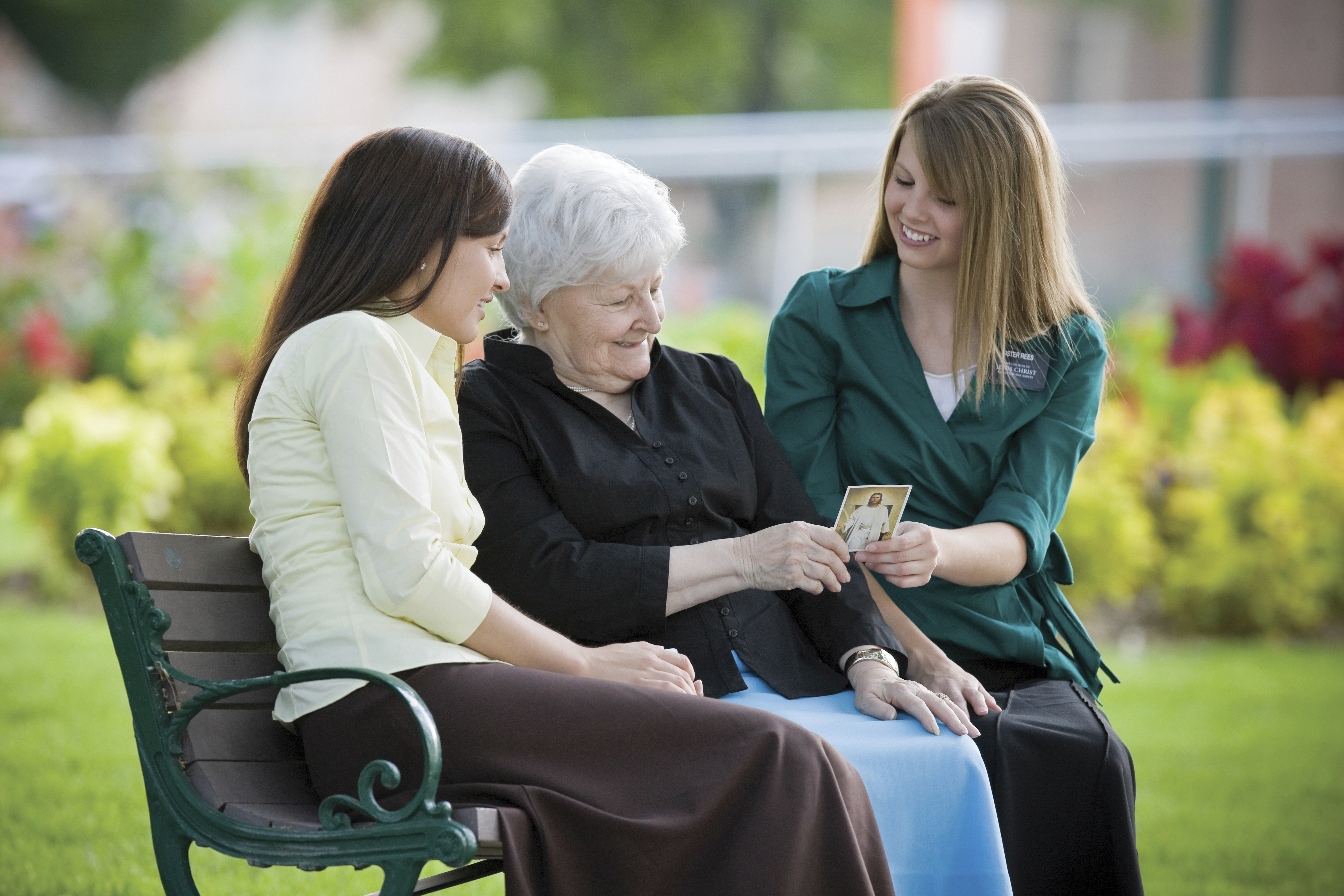 An elderly woman sitting between two sister missionaries and looking at a pass-along card.