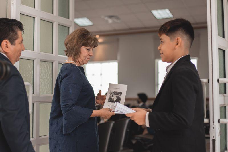 Un niño reparte un folleto a un matrimonio que viene entrando a la capilla