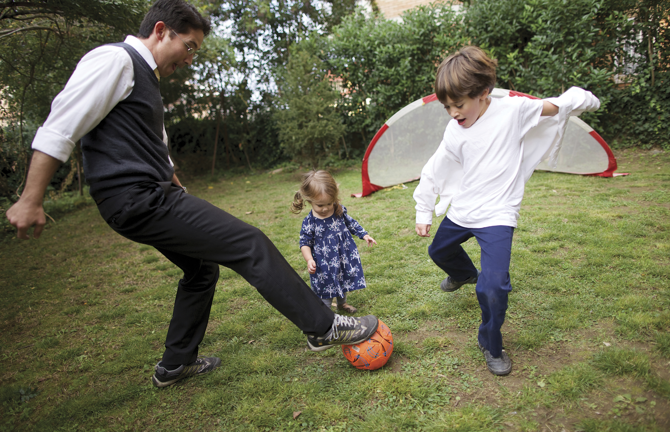 Niki plays soccer with his children.