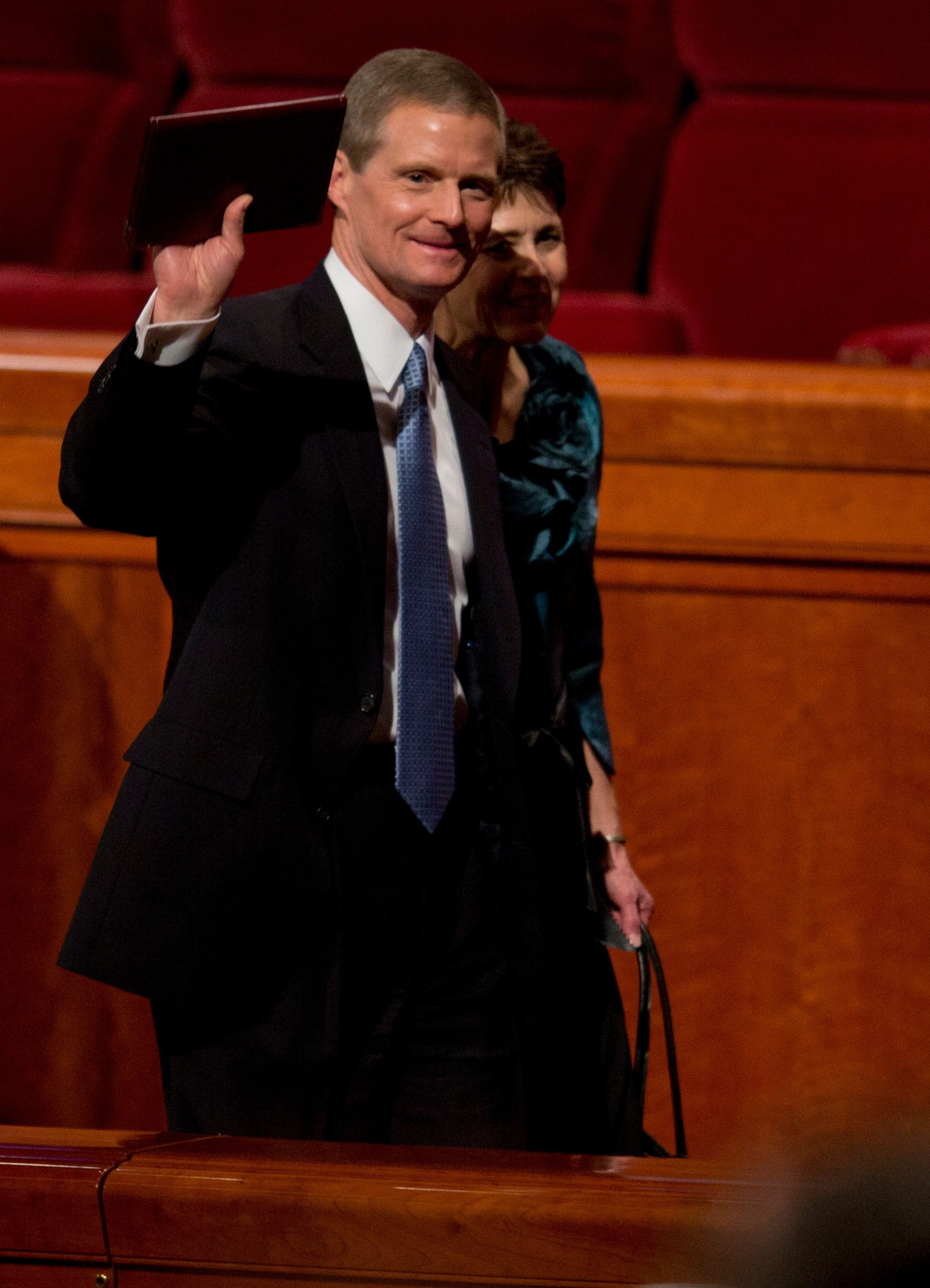 David A. Bednar waving to the congregation as he exits the Conference Center alongside his wife, Susan.