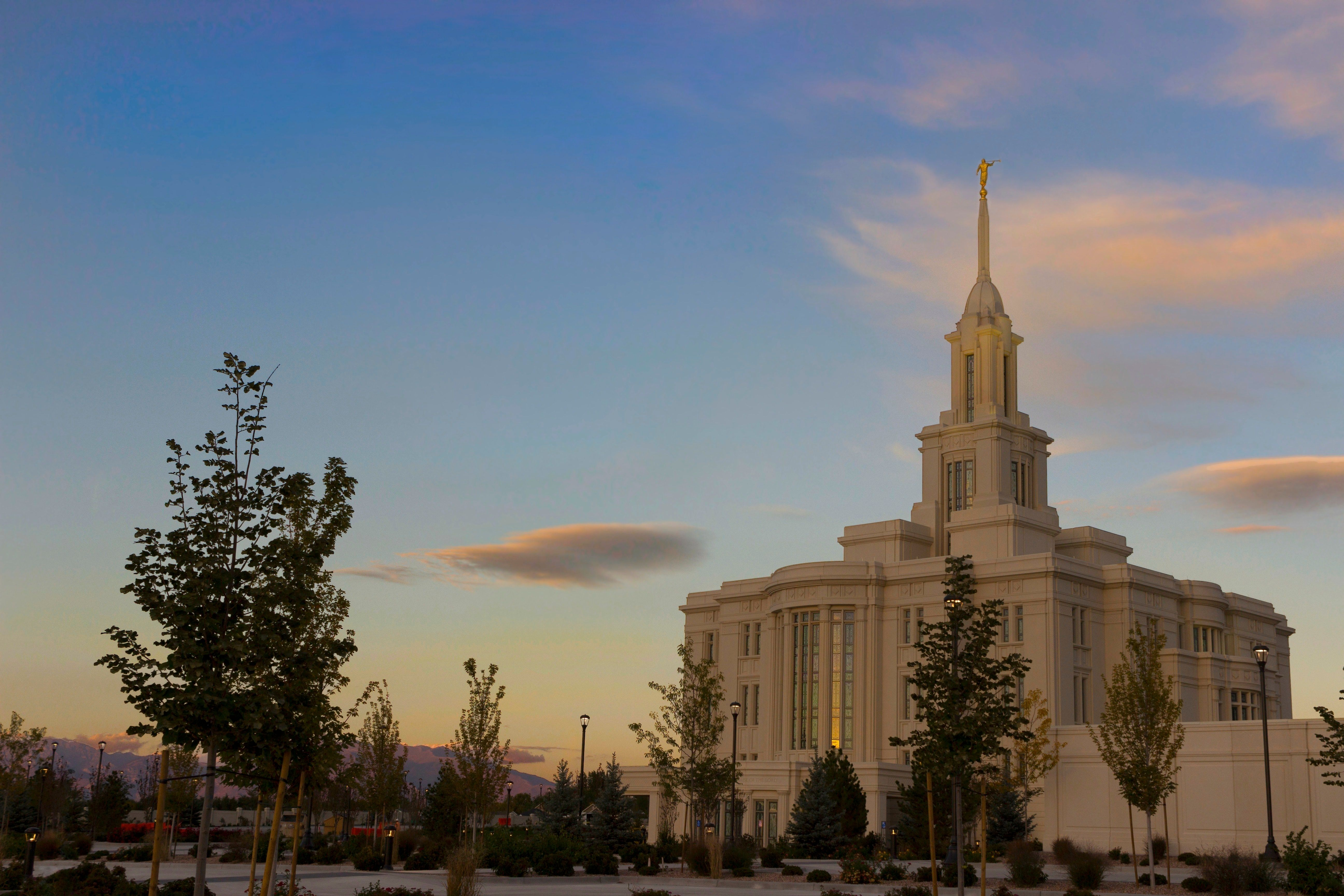 A side view of the Payson Utah Temple during the evening, including scenery.