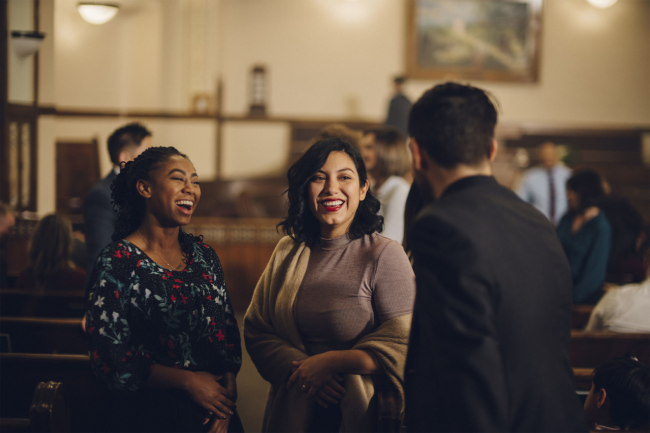 Two woman chat with a man in a church discussing the benefits of attending church and sacrament meeting