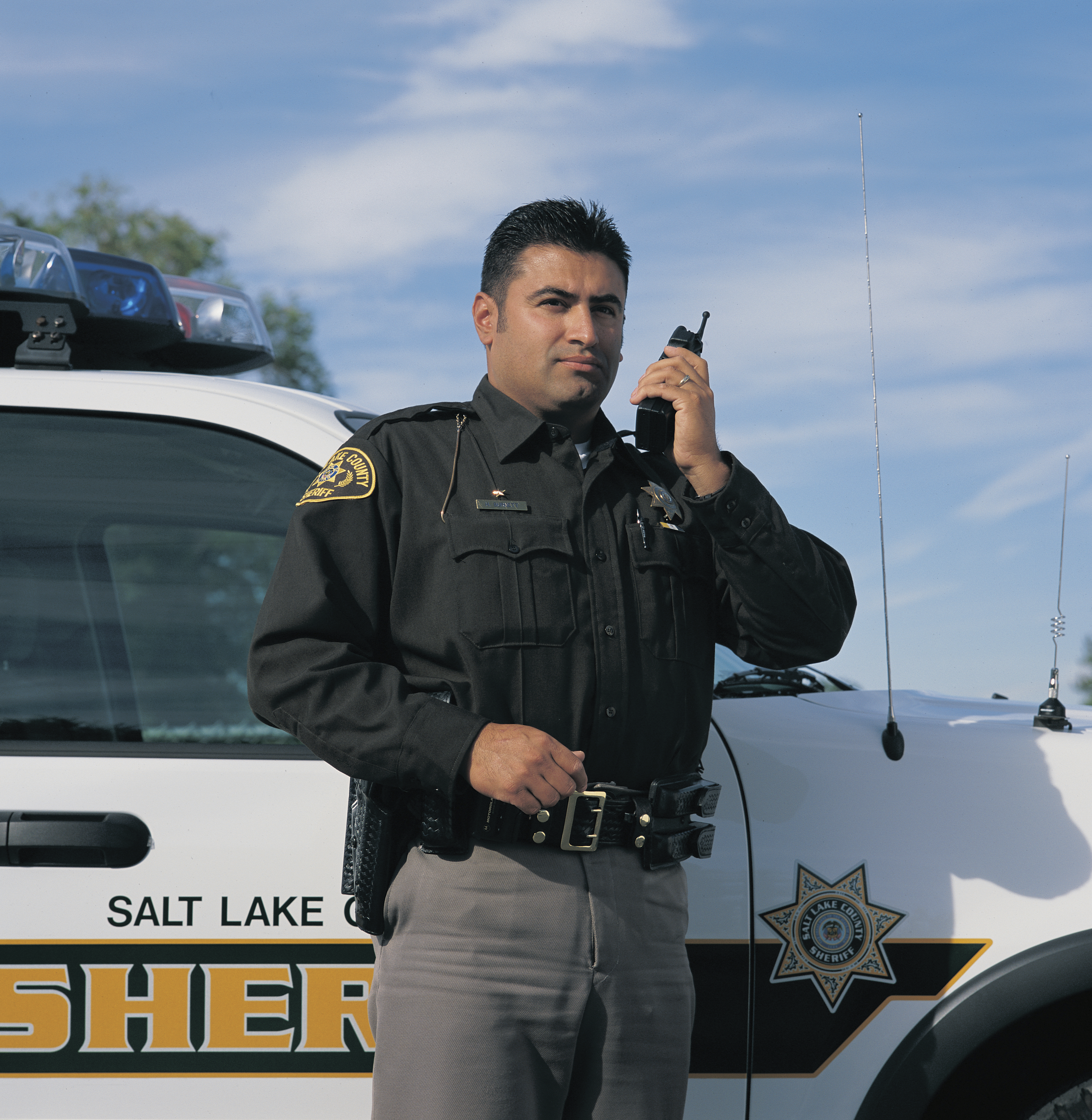 A police officer standing next to his vehicle.