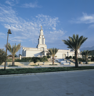 A view from afar of the Monterrey Mexico Temple, with its landscape of palm trees and other plants framing the entrance.