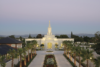 Two sidewalks, palm trees, and lights leading to the entrance of the Córdoba Argentina Temple in the evening.
