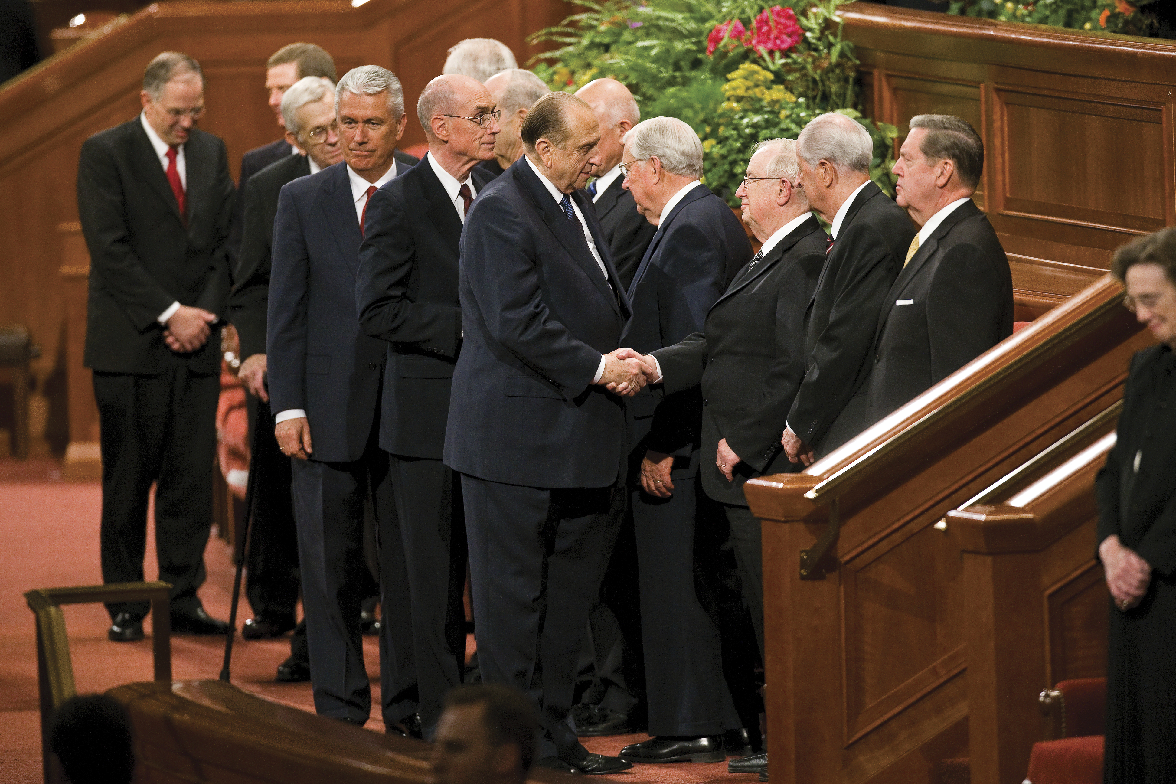 Thomas S. Monson shakes hands with members of the Quorum of the Twelve Apostles on the stand at the Conference Center.