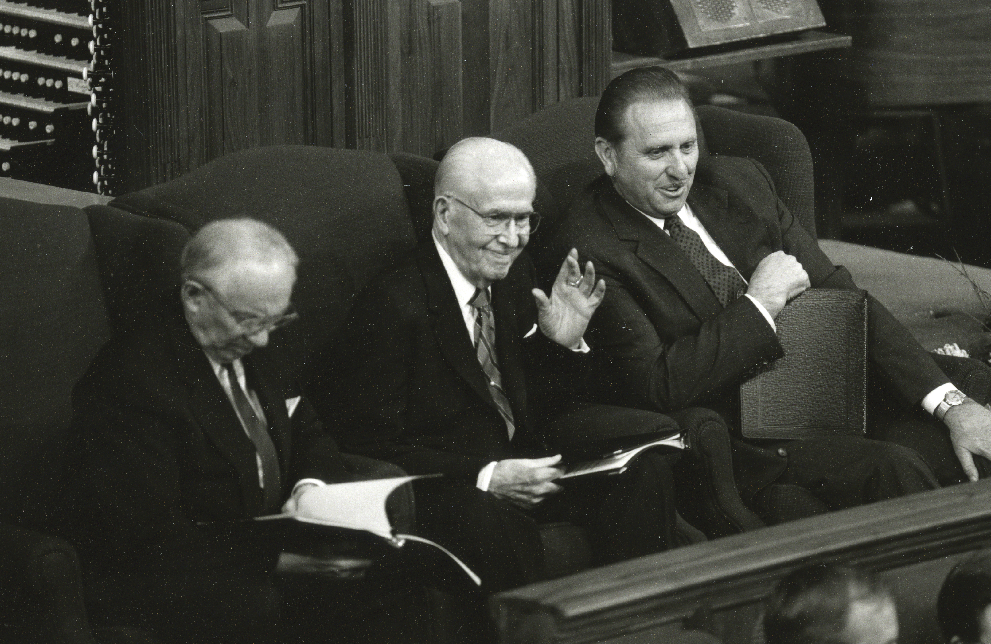 President Benson sitting between his counselors and waving to the audience in the Tabernacle.