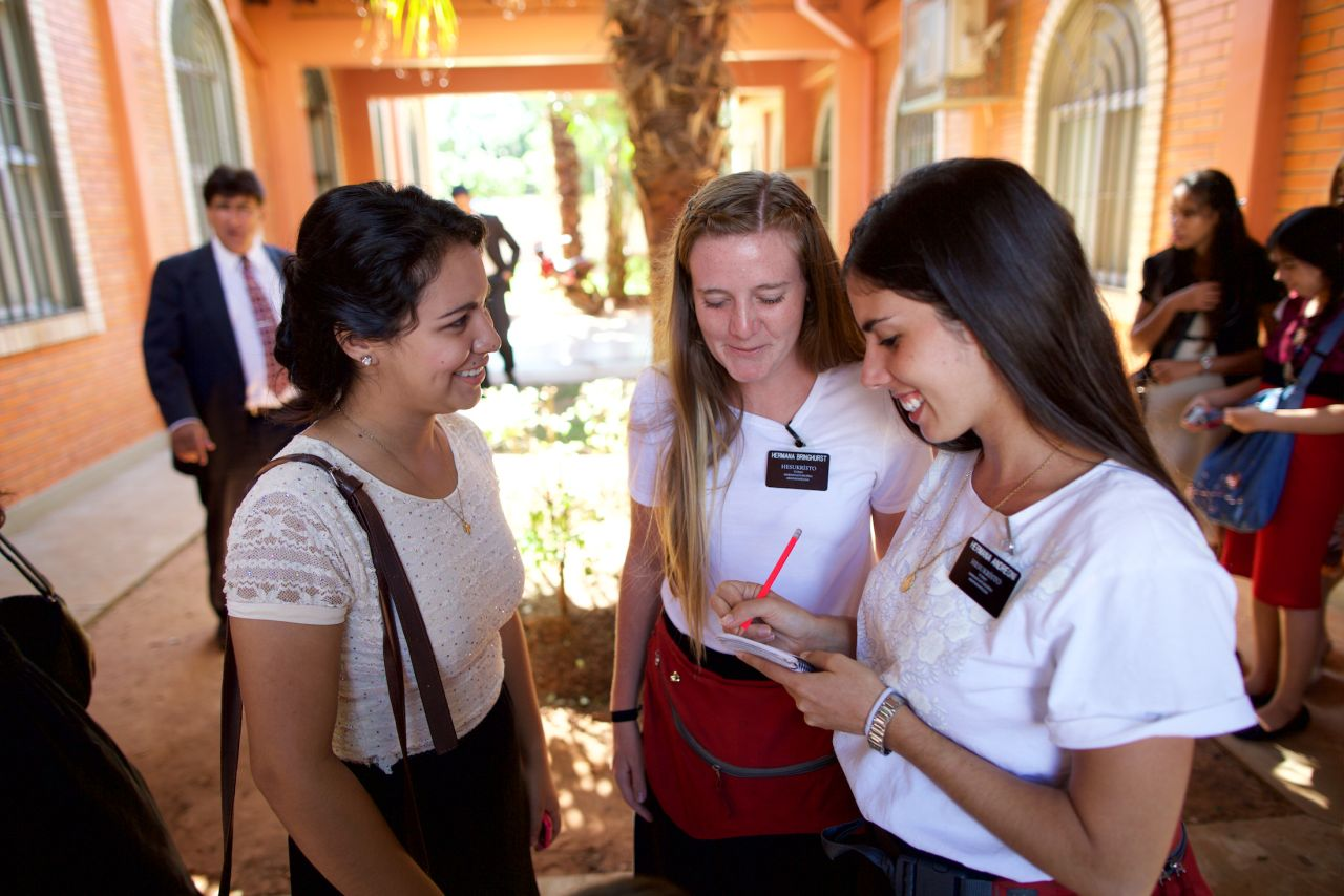 Two sister missionaries teach someone about the gospel of Jesus Christ through a video call