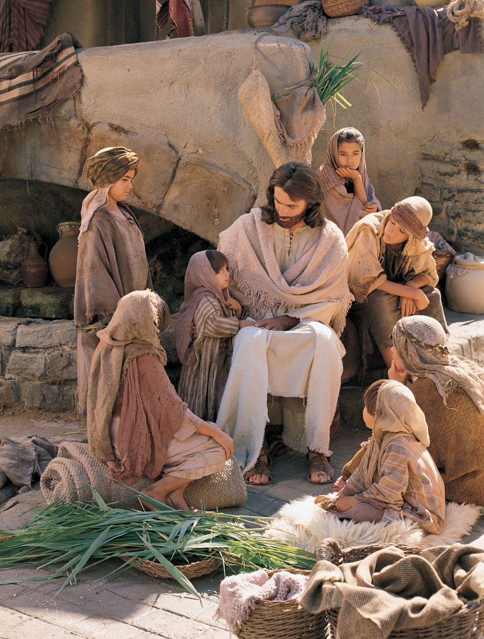 A reenactment showing Christ sitting with a group of children.