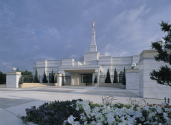 The Oklahoma City Oklahoma Temple during the day, with spring flowers in a flower bed in front of the temple.